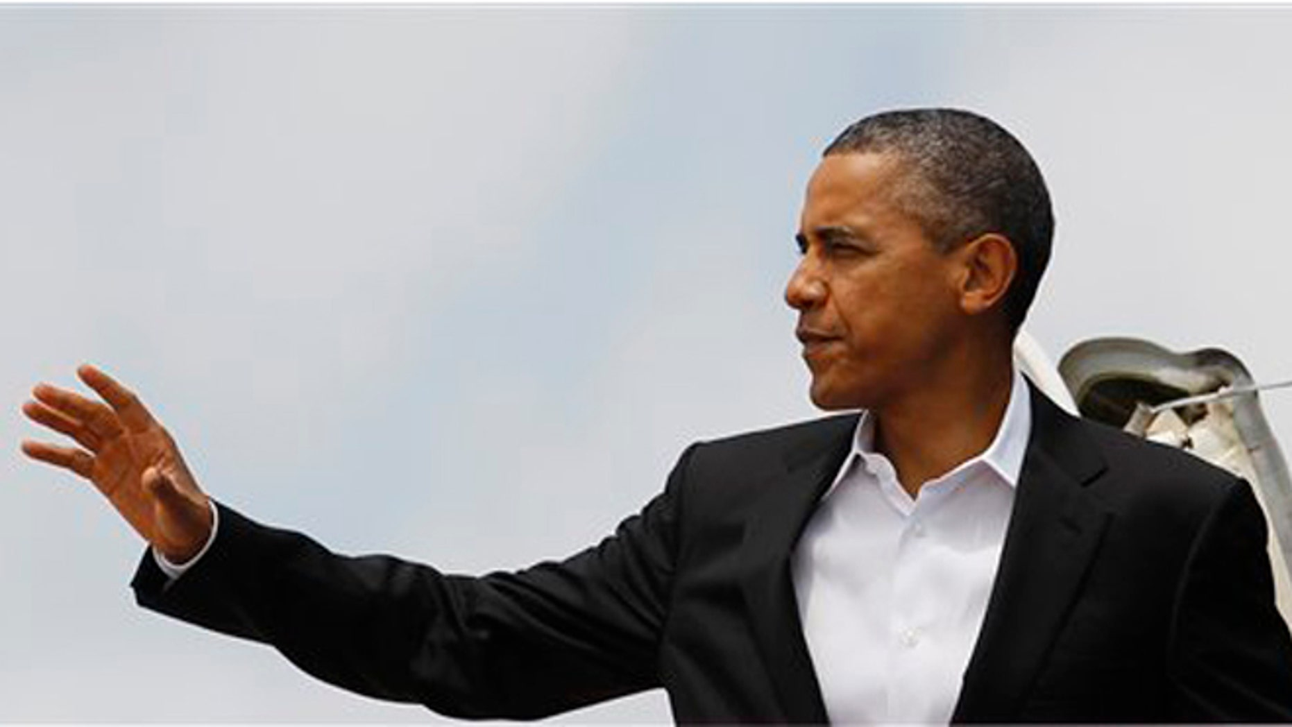 Aug. 11, 2012: President Barack Obama moves to wave as he boards Air Force One, in Andrews Air Force Base, Md., en route to Chicago.