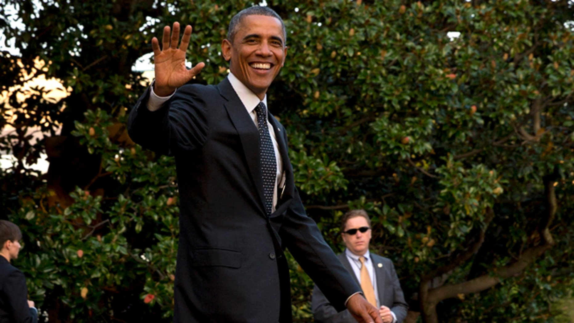 In this Wednesday, Oct. 1, 2014 photo, President Barack Obama waves as he leaves the White House to board the Marine One helicopter en route to Chicago from Washington,
