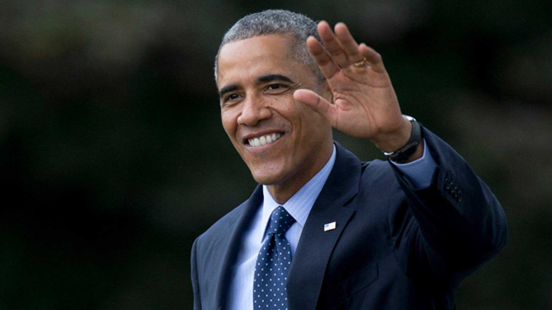 In this Tuesday, Oct. 7, 2014 photo, President Barack Obama waves as he walks across the South Lawn of the White House in Washington.