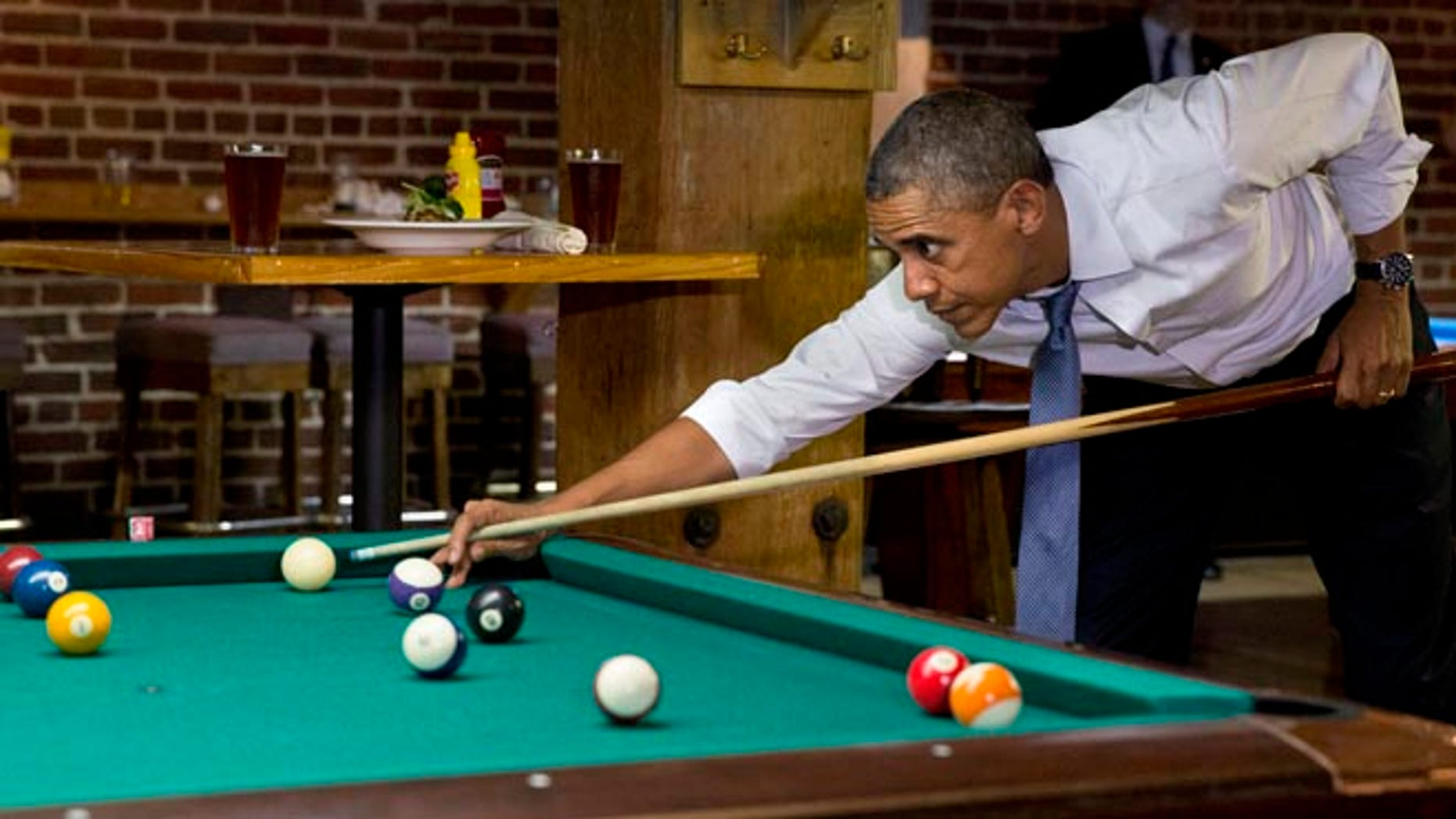 President Barack Obama plays pool at Wynkoop Brewing Co. with Colorado Gov. John Hickenlooper, not seen, Tuesday, July 8, 2014, in Denver.