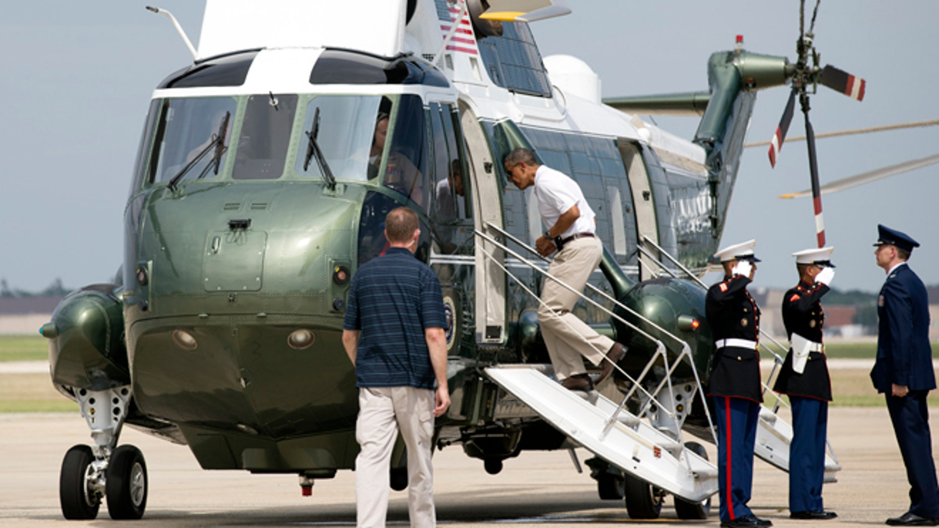 Aug 3, 2013: President Barack Obama, second from left, jogs up the ramp of Marine One as he leaves Andrews Air Force Base, Md., for a weekend in Camp David.