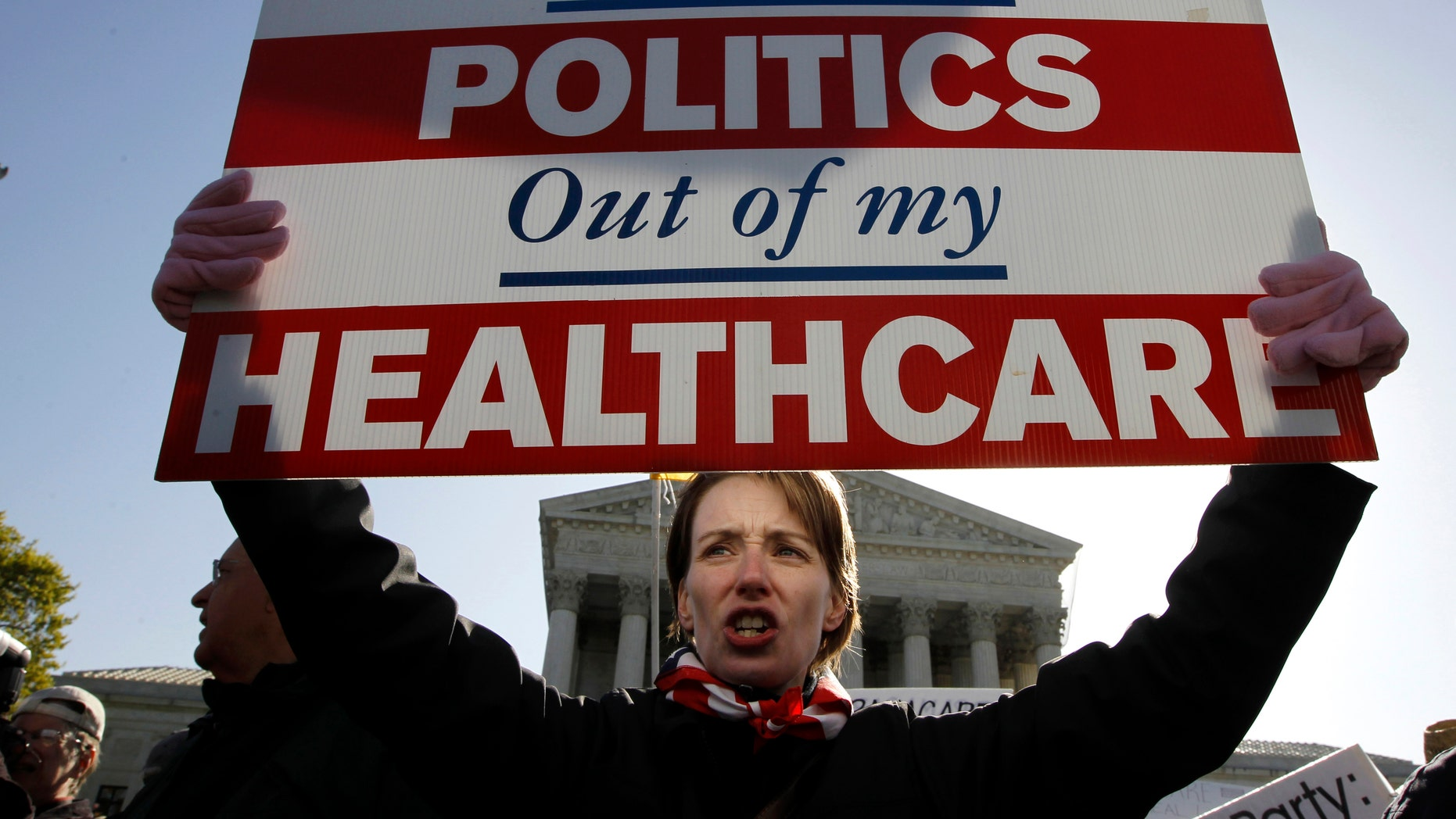 FILE - In this March 27, 2012, file photo, Amy Brighton of Medina, Ohio, who opposes health care reform, rallies in front of the Supreme Court  in Washington. Health care was the defining political battle of President Barack Obamas first term, and _ after the economy_ it remains his most complicated policy challenge at home, central to his place in history.(AP Photo/Charles Dharapak, File)