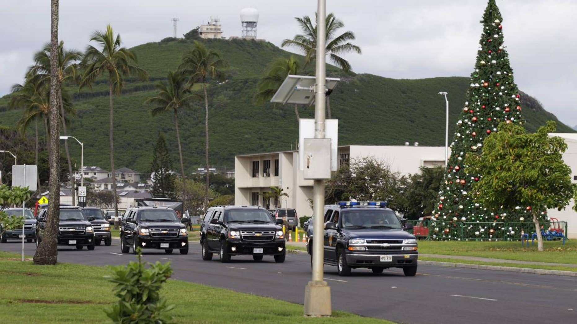 President Barack Obama and first lady Michelle Obama travel by motorcade on Marine Corps Base Hawaii in Kaneohe, Hawaii, Monday, Dec. 27, 2010. (AP Photo/Carolyn Kaster)