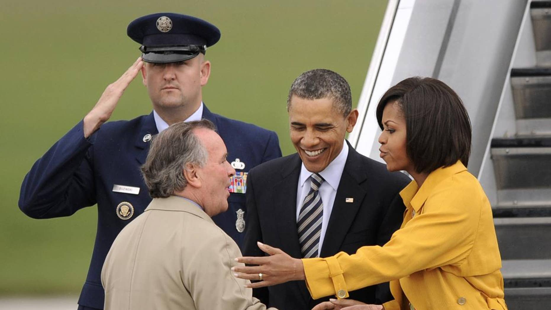 President Barack Obama and first lady Michelle Obama are greeted by Chicago Mayor Richard M. Daley upon their arrival at Chicago O'Hare International Airport in Chicago, Wednesday, April 27, 2011. (AP Photo/Paul Beaty)