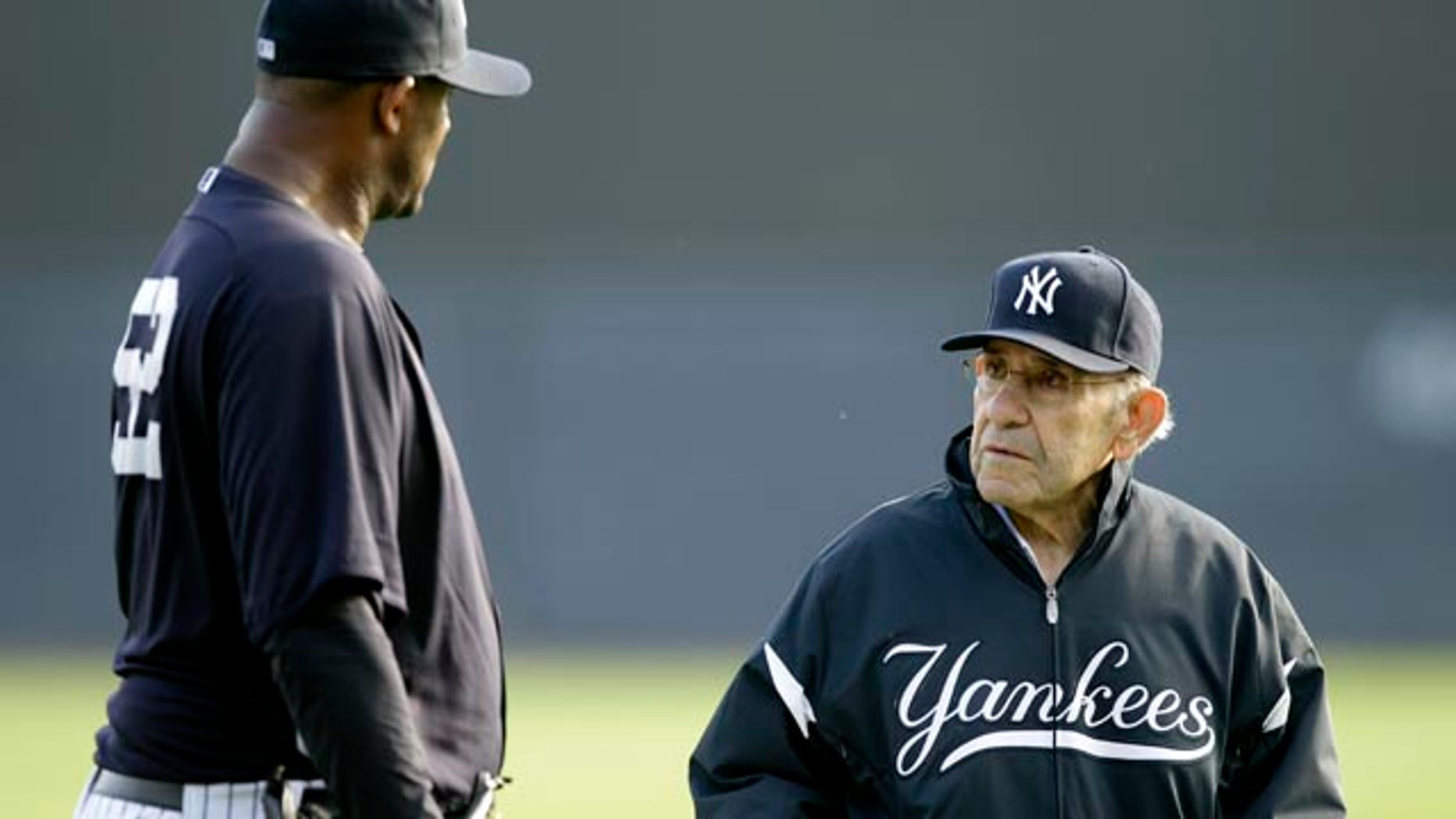 File-This Feb. 24, 2011, file photo shows New York Yankees pitcher CC Sabathia,left, talking with Yogi Berra, right, during a baseball spring training workout at Steinbrenner Field in Tampa, Fla. (AP Photo/Charlie Neibergall, File)