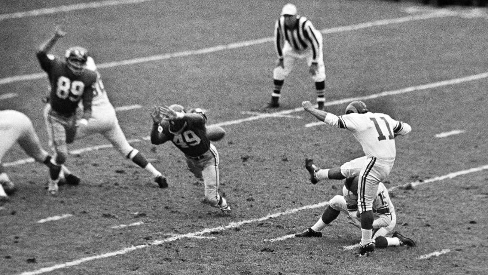 FILE -  In this Oct. 22, 1961, file photo, New York Giants halfback Erich Barnes (49) blocks field goal-attempt by Los Angeles Rams' Danny Villanueva (11) in the first period of NFL game in New York's Yankee Stadium. Villanueva, who was one of the NFL's first Latino kickers and a pioneer of Spanish-language television, has died. He was 77. Family members and officials at New Mexico State University, where Villanueva was a member of the athletic hall of fame, confirmed that he died Thursday, June 18, 2015, after suffering a stroke earlier this week. (AP Photo, File)