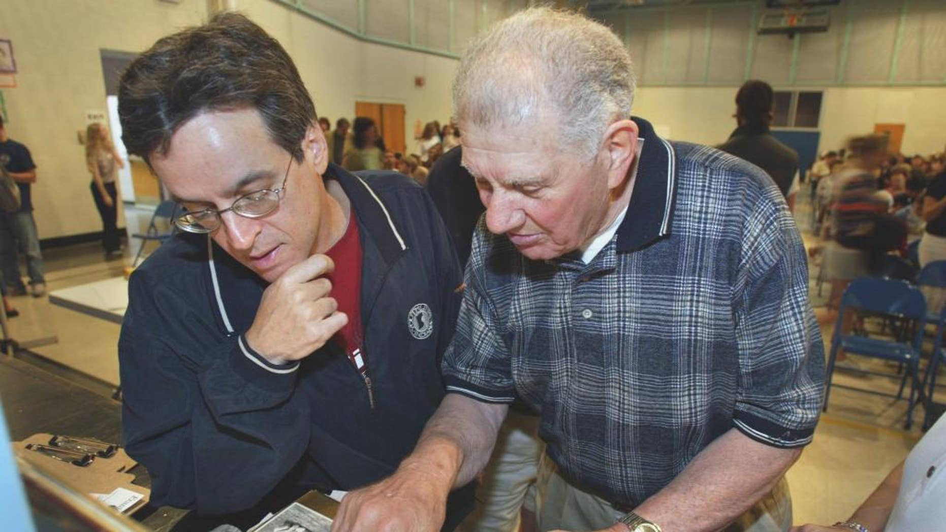 """FILE - In this May 31, 2003, file photo, screenwriter Angelo Pizzo, left, looks at some old photos with former United States soccer player Frank Borghi at Shaw School during a casting call for the movie """"The Game of Their Lives,"""" in St. Louis.  Borghi, the goalkeeper in the United States' 1-0 upset victory over England in the 1950 World Cup, died Monday, Feb. 2, 2015, according to the St. Louis Soccer Hall of Fame. He was 89. (AP Photo/St. Louis Post-Dispatch, Teak Phillips, File)  EDWARDSVILLE INTELLIGENCER OUT; THE ALTON TELEGRAPH OUT"""
