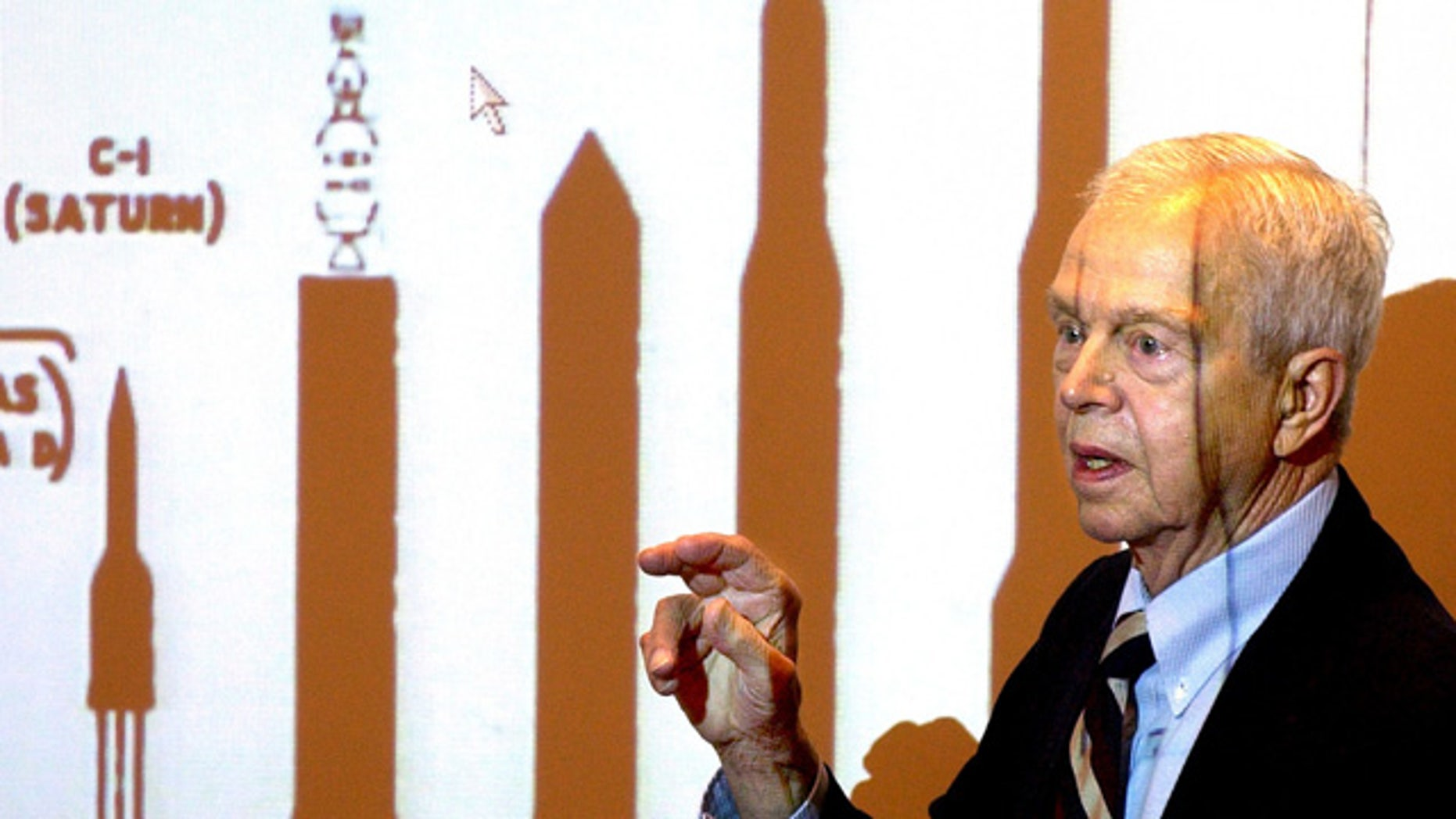 File-This Oct. 9, 2003, file photo shows John C. Houbolt explaining the size of different rockets required to launch various methods for landing on the moon at Grainger Engineering Library in Urbana, Ill. (AP Photo/News-Gazette, John Dixon, File)