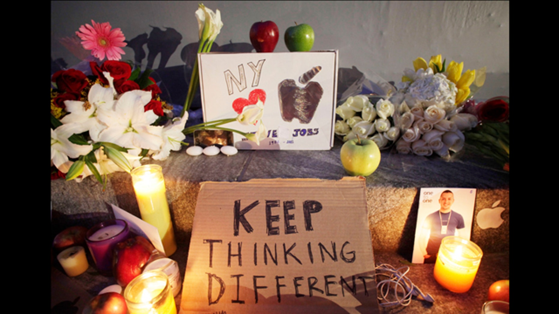 Candles illuminate a memorial to Apple co-founder Steve Jobs, Thursday, Oct. 6, 2011 in front of an Apple store in New York. Jobs died Wednesday at 56.