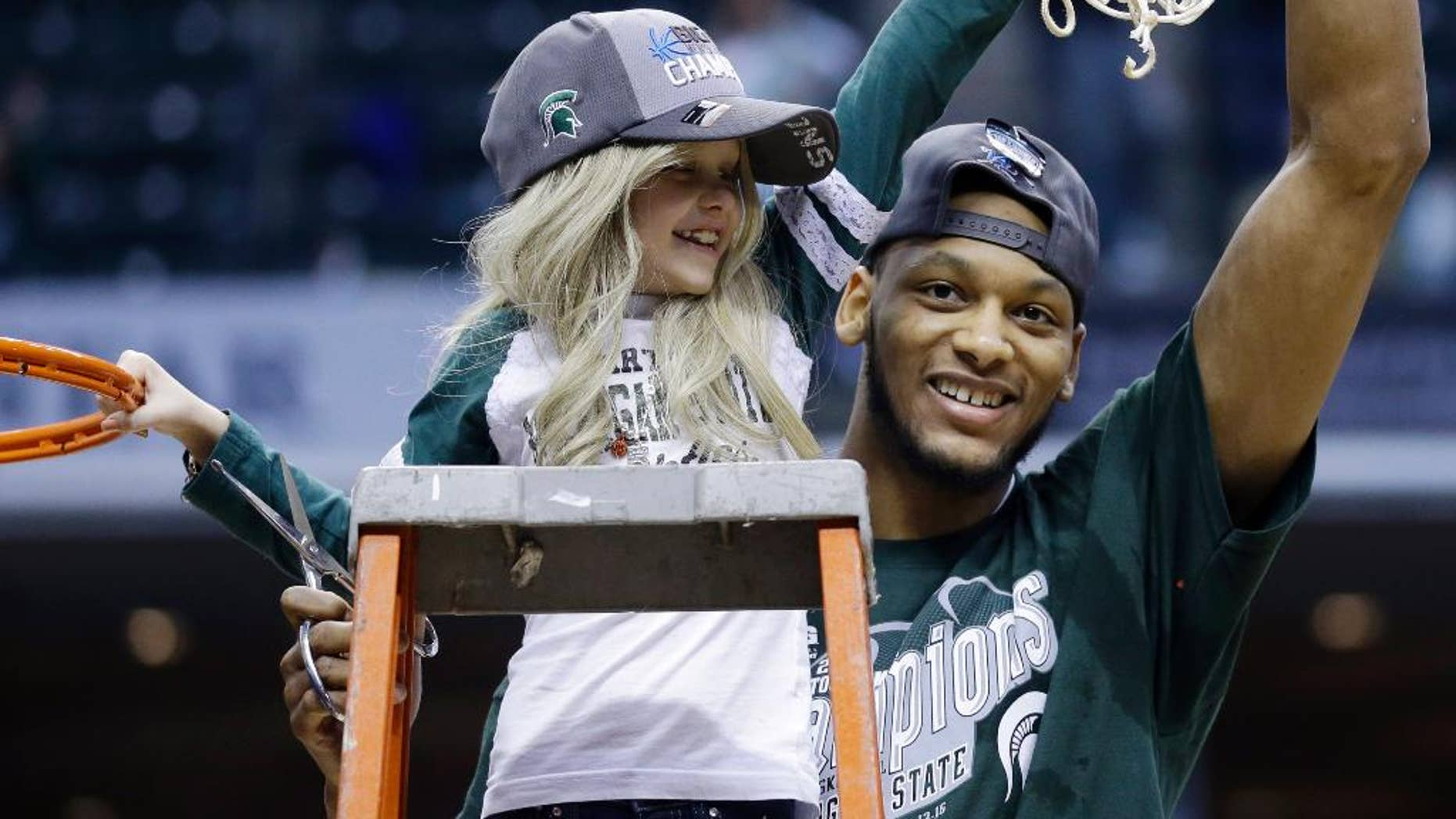 """FILE - In this March 16, 2014 file photo, Michigan State forward Adreian Payne, right, hoists the net with Lacey Holsworth, who is battling cancer, after Michigan State defeated Michigan 69-55 in an NCAA college basketball game in the championship of the Big Ten Conference tournament in Indianapolis. The father of  8-year-old Lacey Holsworth, who befriended Michigan State basketball star Adreian Payne says his daughter has died. Matt Holsworth says Lacey Holsworth died at their St. Johns, Mich., home late Tuesday, April 8, 2014 """"with her mommy and daddy holding her in their arms."""" (AP Photo/Michael Conroy, File)"""