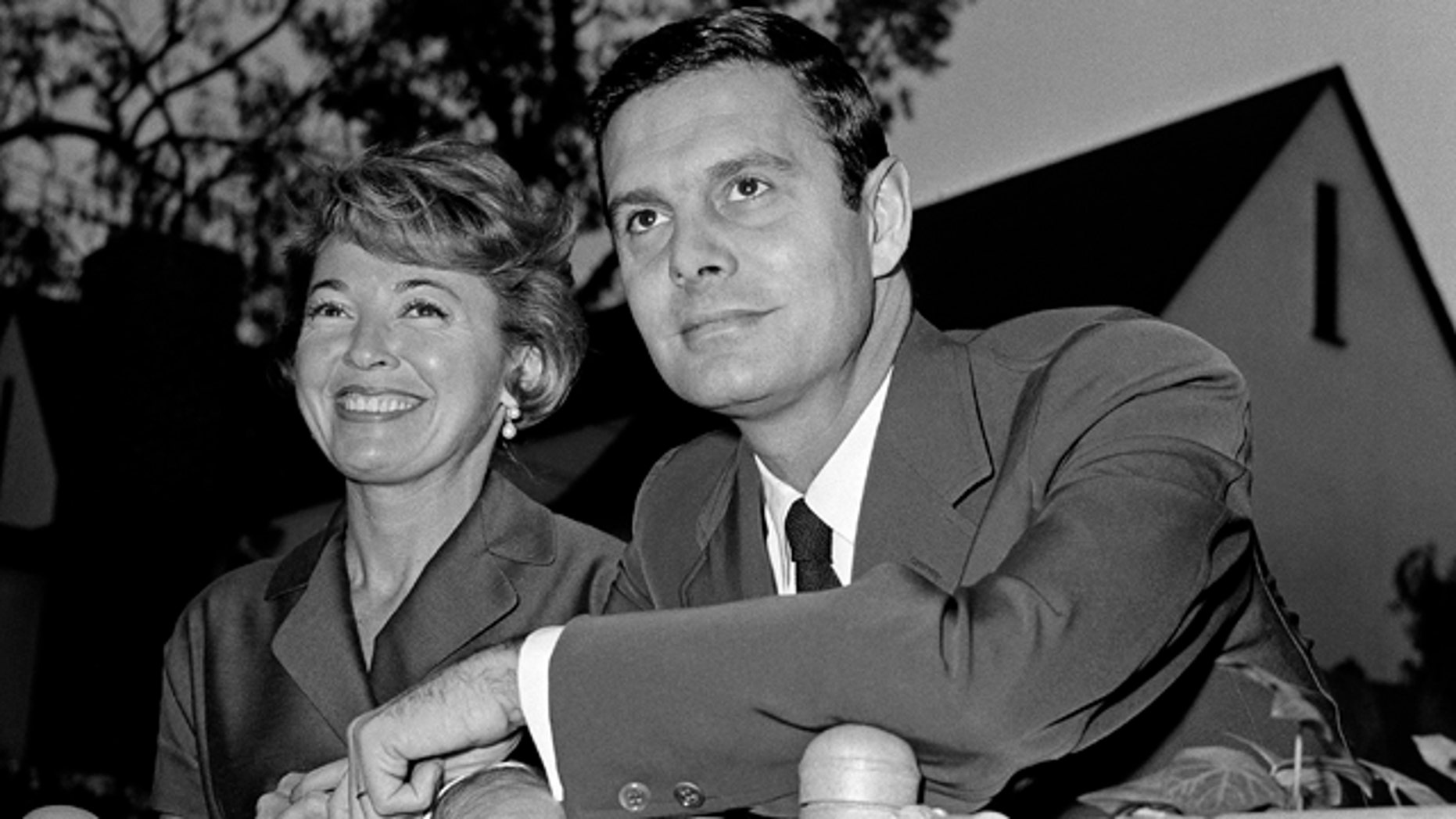 """In this Jan. 5, 1959 file photo, actor Louis Jourdan and his wife Berthe Fredrique pose at their home in Beverly Hills, Calif. Jourdan, the dashingly handsome Frenchman who starred in """"Gigi,"""" ''Can-Can,"""" ''Three Coins in the Fountain"""" and other American movies, has died on Saturday, Feb. 14, 2015. He was 93. (AP Photo, File)"""