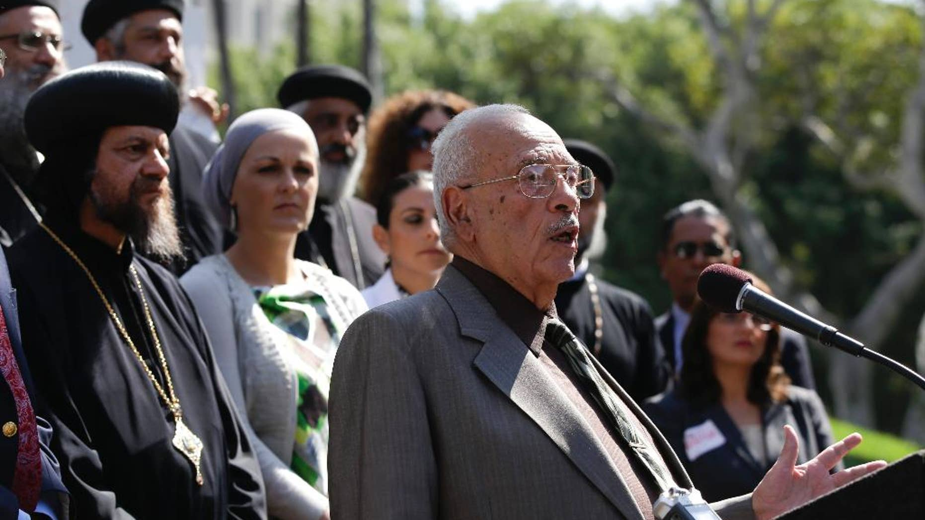 FILE - In this Sept. 17, 2012, file photo, Dr. Maher Hathout, Senior Adviser of the Muslim Public Affairs Council, center, speaks in Los Angeles to condemn all violent reactions in the Middle East. Hathout, a prominent interfaith leader, hailed as the father of the American Muslim identity, has died at age 79. Salam al-Marayati, president of the Muslim Public Affairs Council that Hathout co-founded, says Hathout died Friday, Jan. 2, 2015, after a yearlong battle with liver cancer.  (AP Photo/Chris Carlson, File)