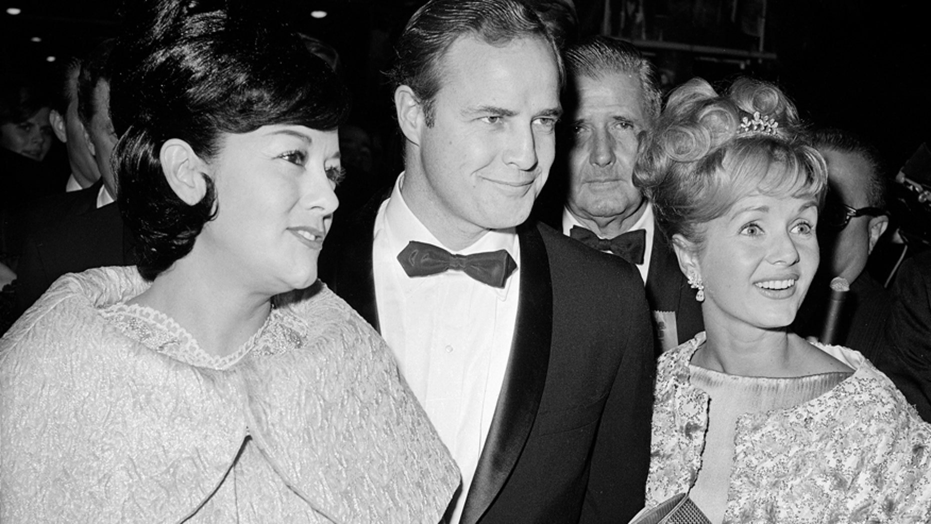 """FILE-This Nov. 15, 1962 file photo shows Marlon Brando, his wife, Mexican actress Movita Castaneda, left, and actress Debbie Reynolds, right, arriving for the West Coast premiere of """"Mutiny on the Bounty"""" at the Hollywood Egyptian Theater in Los Angeles. Castaneda, the dark-haired actress who met Brando on a movie set and later married him and had two of his children died Thursday, Feb. 12, 2015 at a Los Angeles rehabilitation center after being treated for a neck injury. The Los Angeles Times says Castaneda was believed to be 98."""
