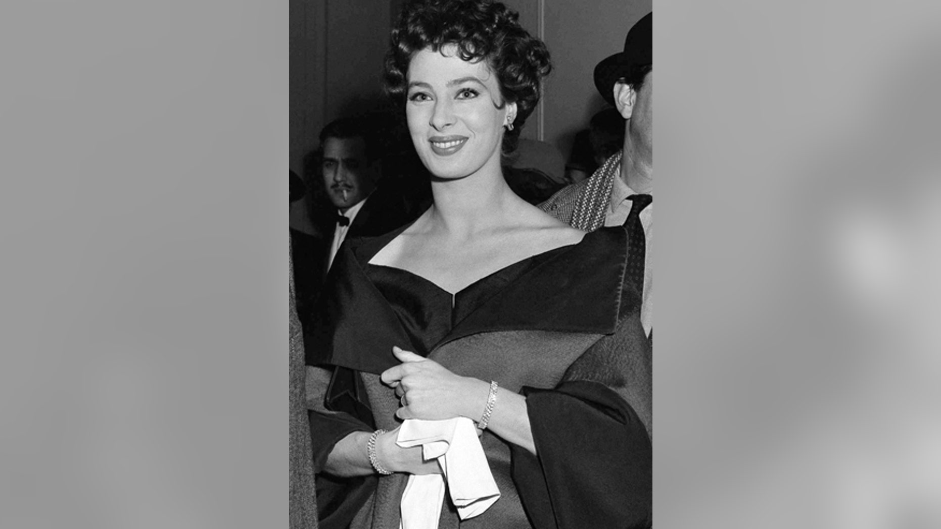 """FILE - In this March 4, 1954, file photo, actress Rita Gam stands in lobby of Longacre Theatre at opening of  """"The Burning Glass"""" in New York."""