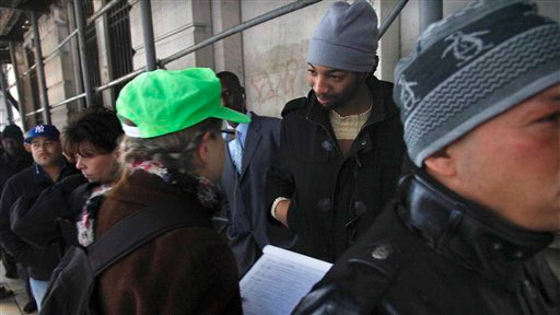 Dec. 14: Hero Vincent, second from right, an early protester in the Occupy Wall Street movement, listens as Judith Anderson, a lawyer working with the National Lawyers Guild, records information about him as he stands in line outside Manhattan Criminal Court on Wednesday.