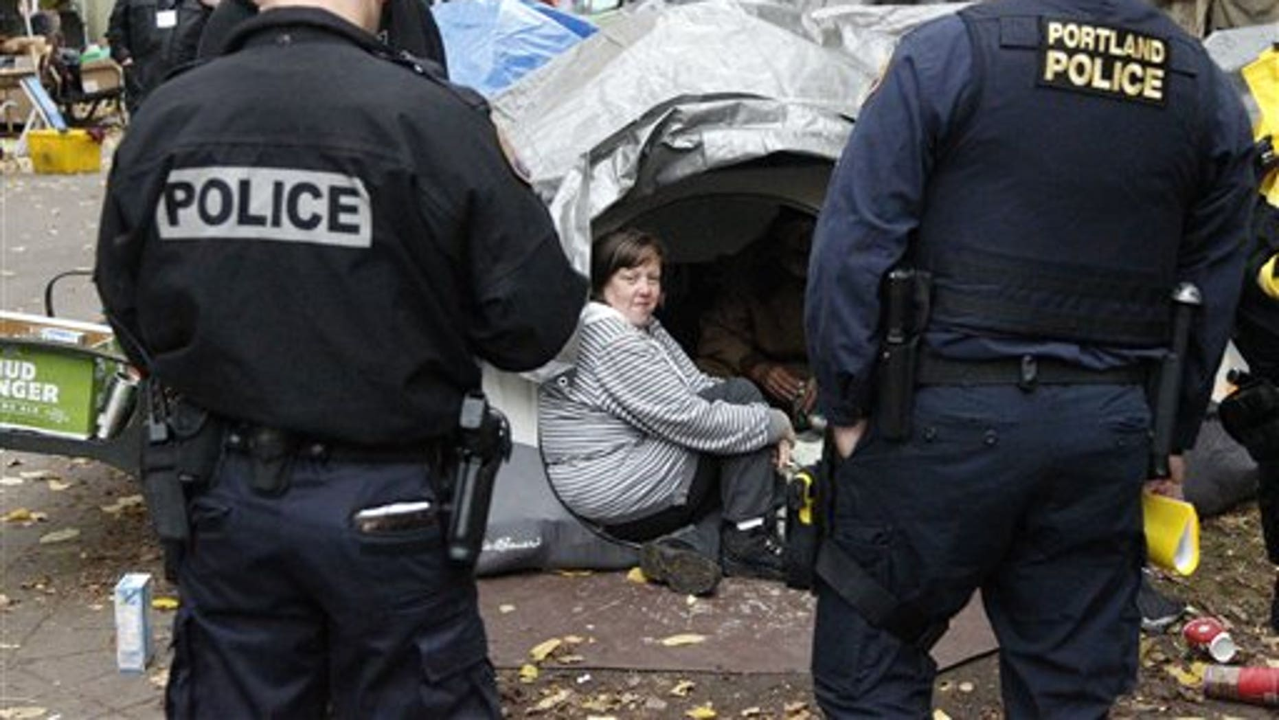 Nov. 11, 2011: Erin Robertson sits in the doorway of a tent while Portland police look on at the Occupy Portland encampment.