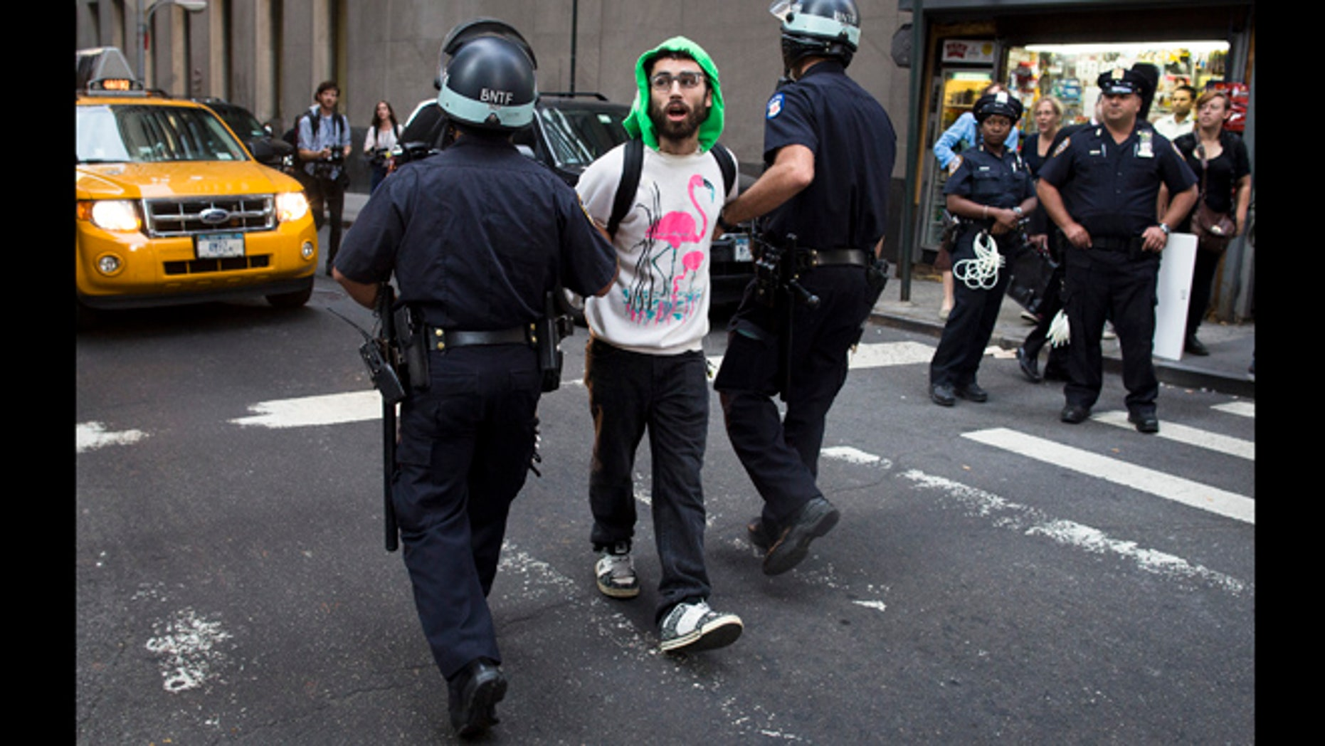 Sept. 17, 2012: An Occupy Wall Street protestor is arrested on Wall Street for blocking pedestrian traffic on a sidewalk in New York. A handful of Occupy Wall Street protestors have been arrested during a march toward the New York Stock Exchange on the anniversary of the grass-roots movement.
