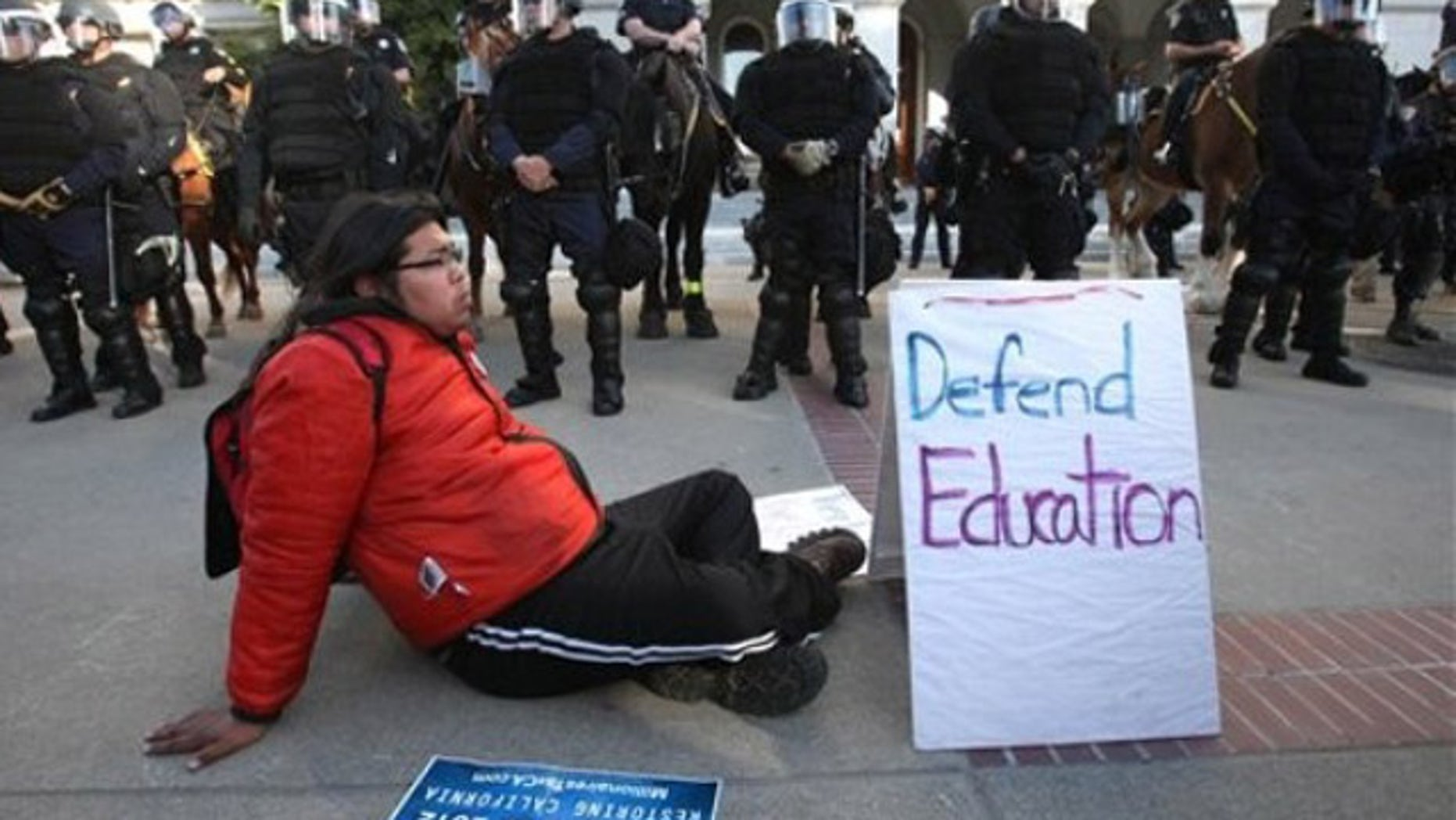 March 5, 2012: Derrick, a member of Occupy San Francisco, sits  in front of California Highway Patrol officers dressed in riot gear during a demonstration against cuts to higher education held at the Capitol in Sacramento, Calif.