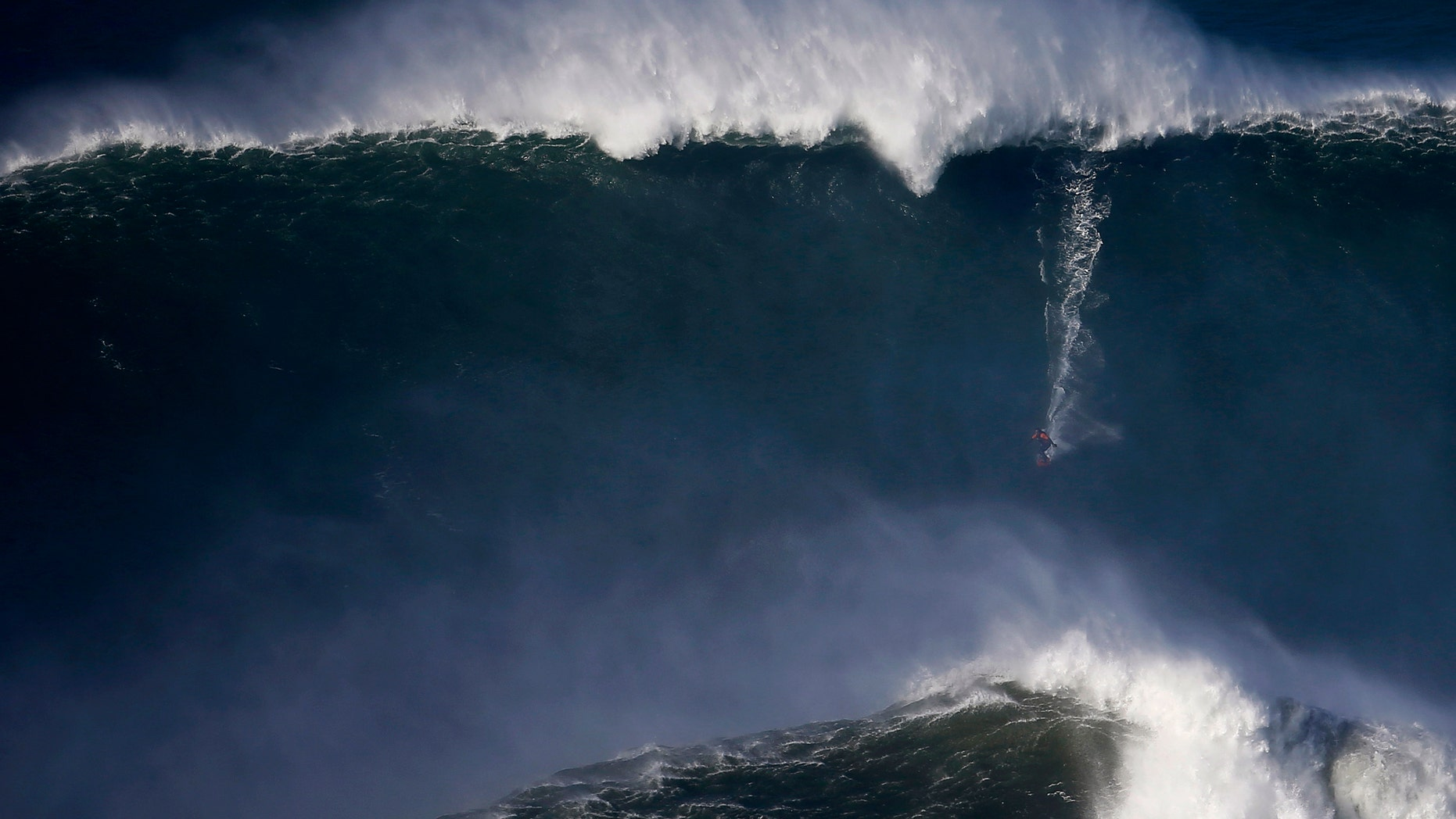 File photo - A surfer drops in on a large wave at Praia do Norte, in Nazare Dec. 11, 2014.