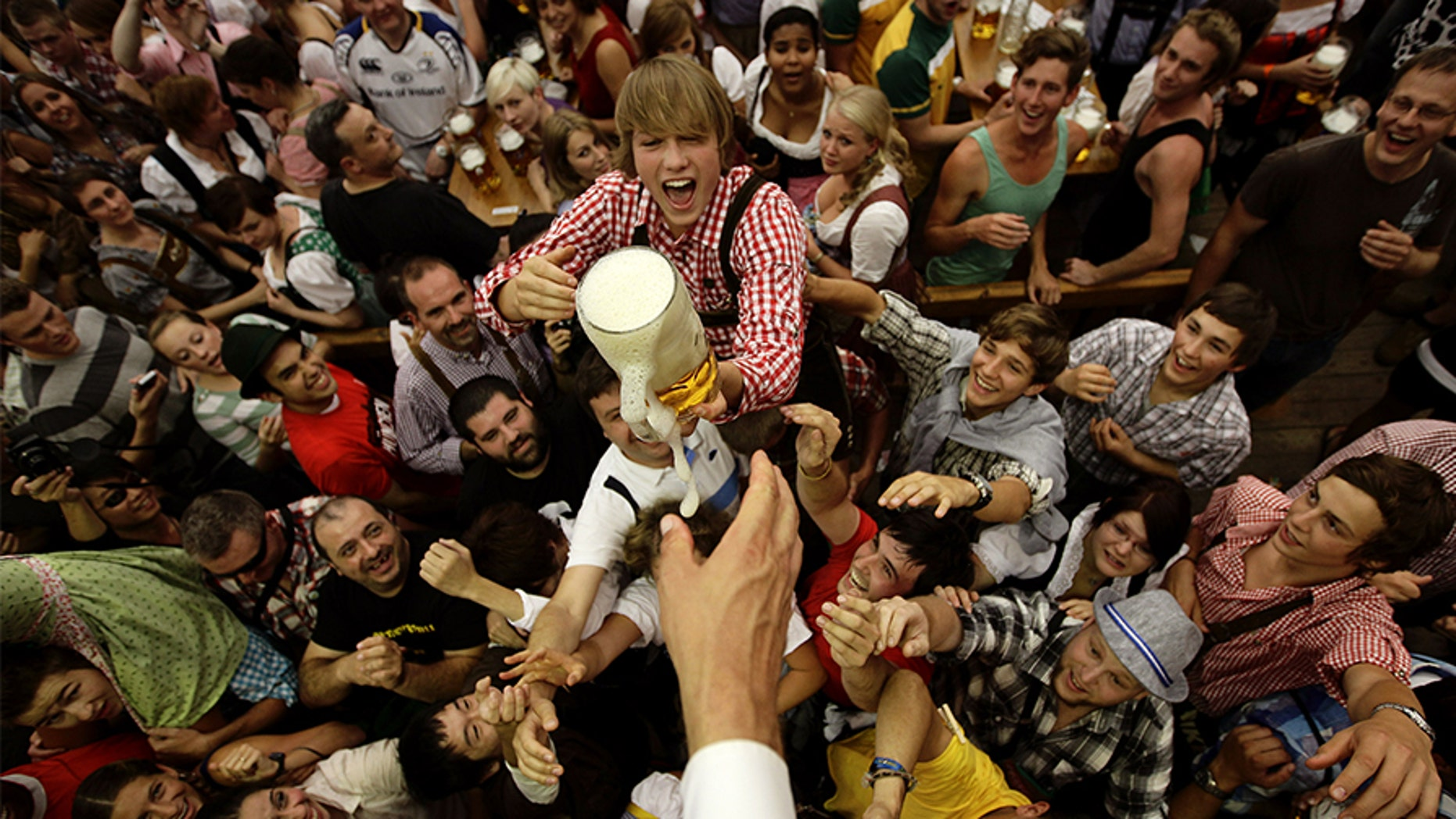 Revelers scuffle for the first free beer in the traditional 1-litre beer mug at the opening of the World's biggest beer fest, the Munich Oktoberfest, at the Theresienwiese in Munich, September 17, 2011.
