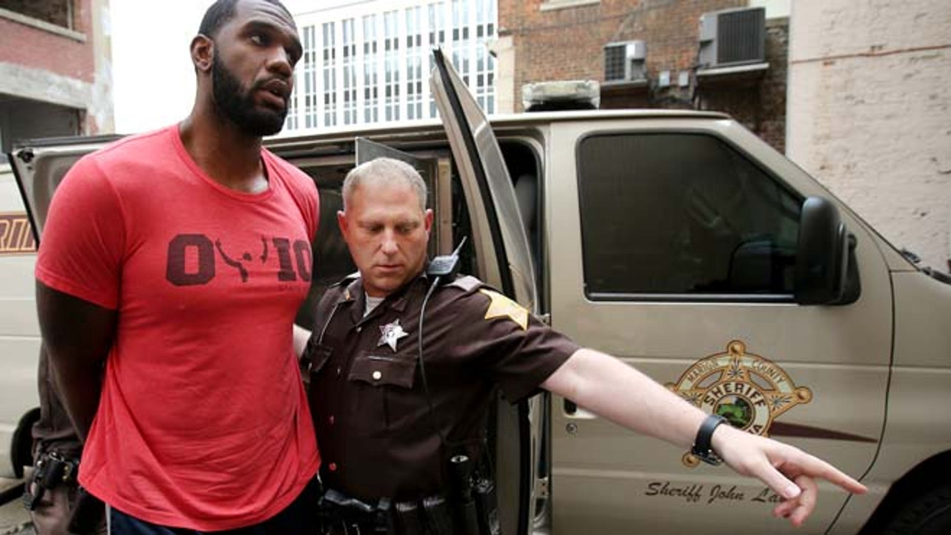 Aug. 7, 2014: Greg Oden is escorted into the Marion County Community Corrections building in Indianapolis. (AP/The Indianapolis Star)