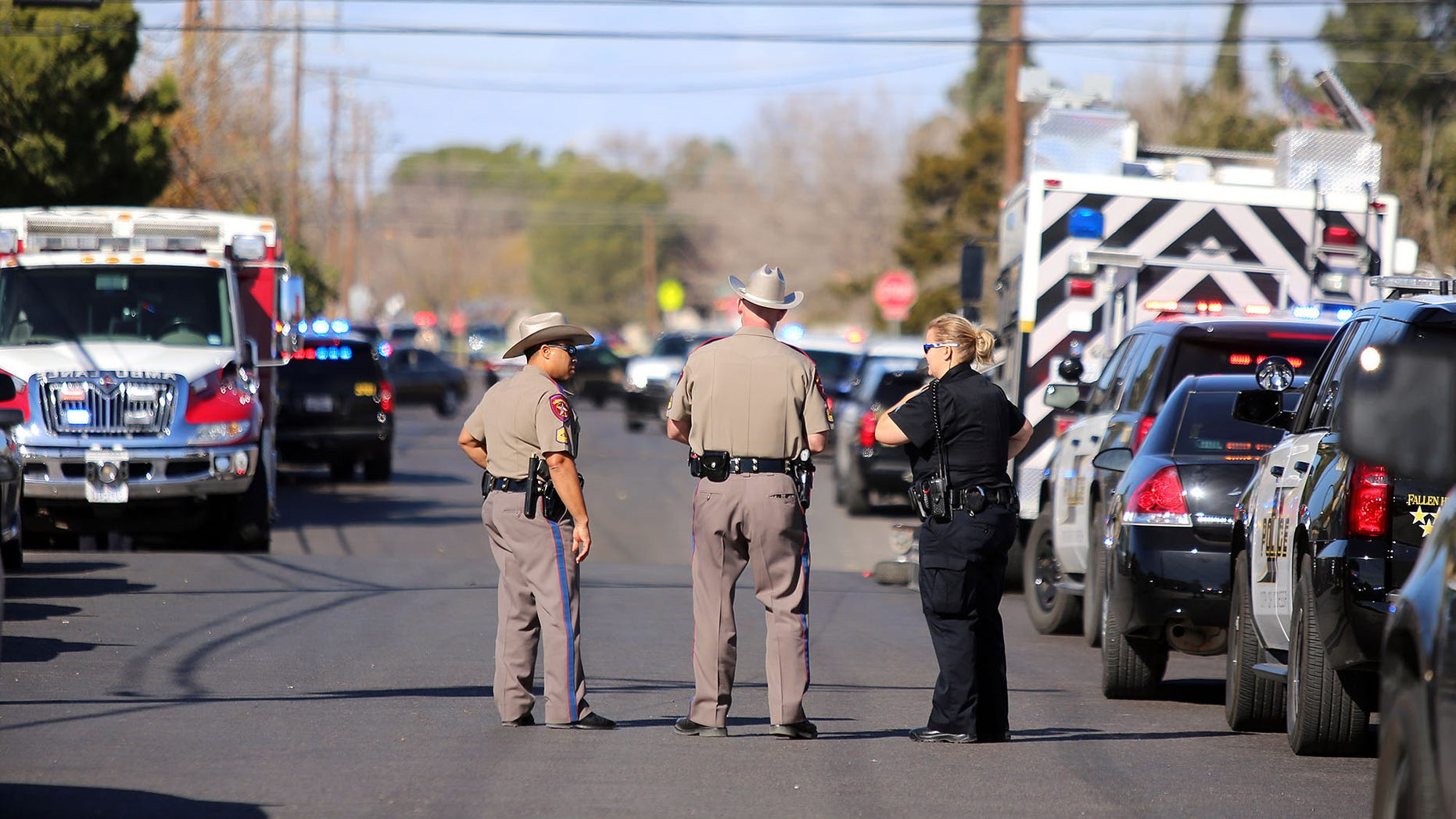 Authorities wait near an apartment complex with a barricaded suspect on Wednesday Dec. 23, 2015, in Odessa, Texas. Authorities say multiple Odessa police officers have been shot while attempting to serve a warrant at the apartment complex, with the suspect barricaded inside. (Edyta Blaszczyk/Odessa American via AP) MANDATORY CREDIT