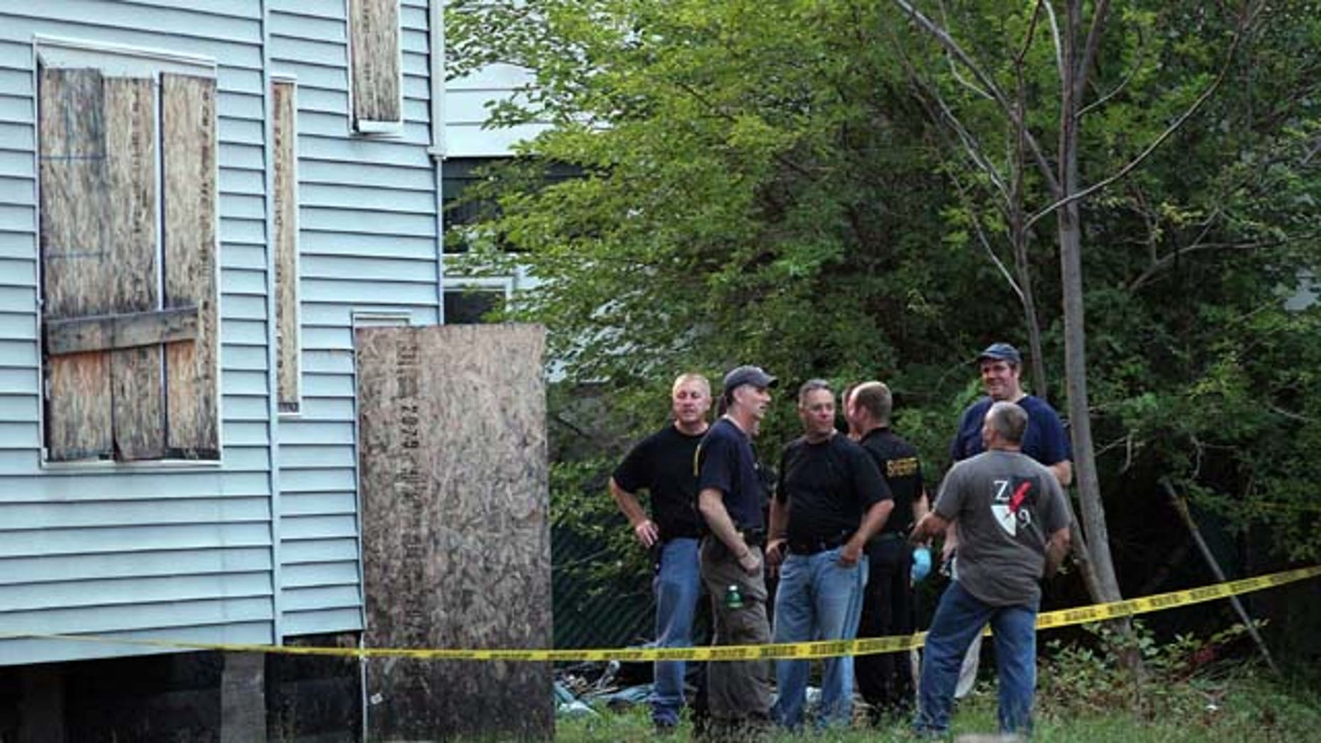 July 20, 2013: Law enforcement and FBI stand at the back of a boarded-up home where bodies were found earlier in the day Saturday in East Cleveland, Ohio. (AP Photo/The Plain Dealer, Joshua Gunter)