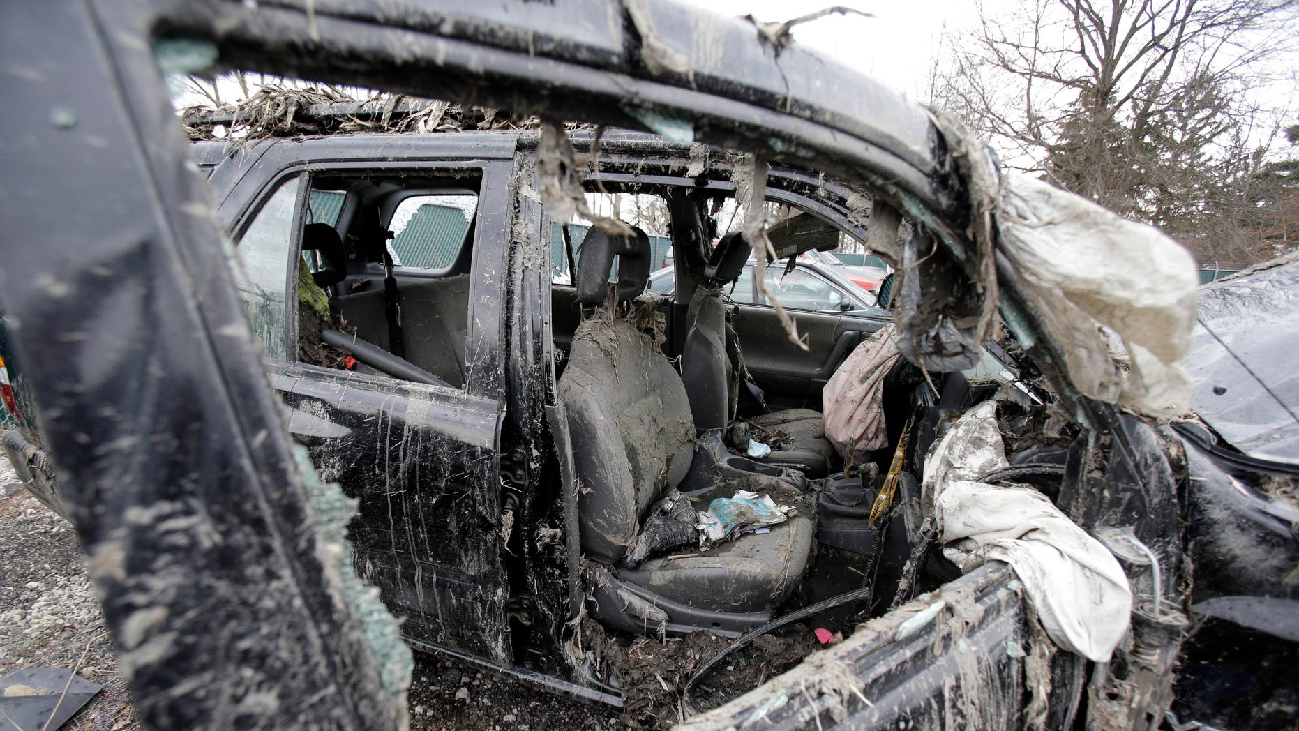 March 11, 2013: Photo in Southington, Ohio shows the vehicle where six people died in a crash early Sunday in Warren, Ohio. Two teens who escaped the crash that killed six friends in a swampy pond wriggled out of the wreckage by smashing a rear window and swimming away from the SUV, a state trooper said Monday.