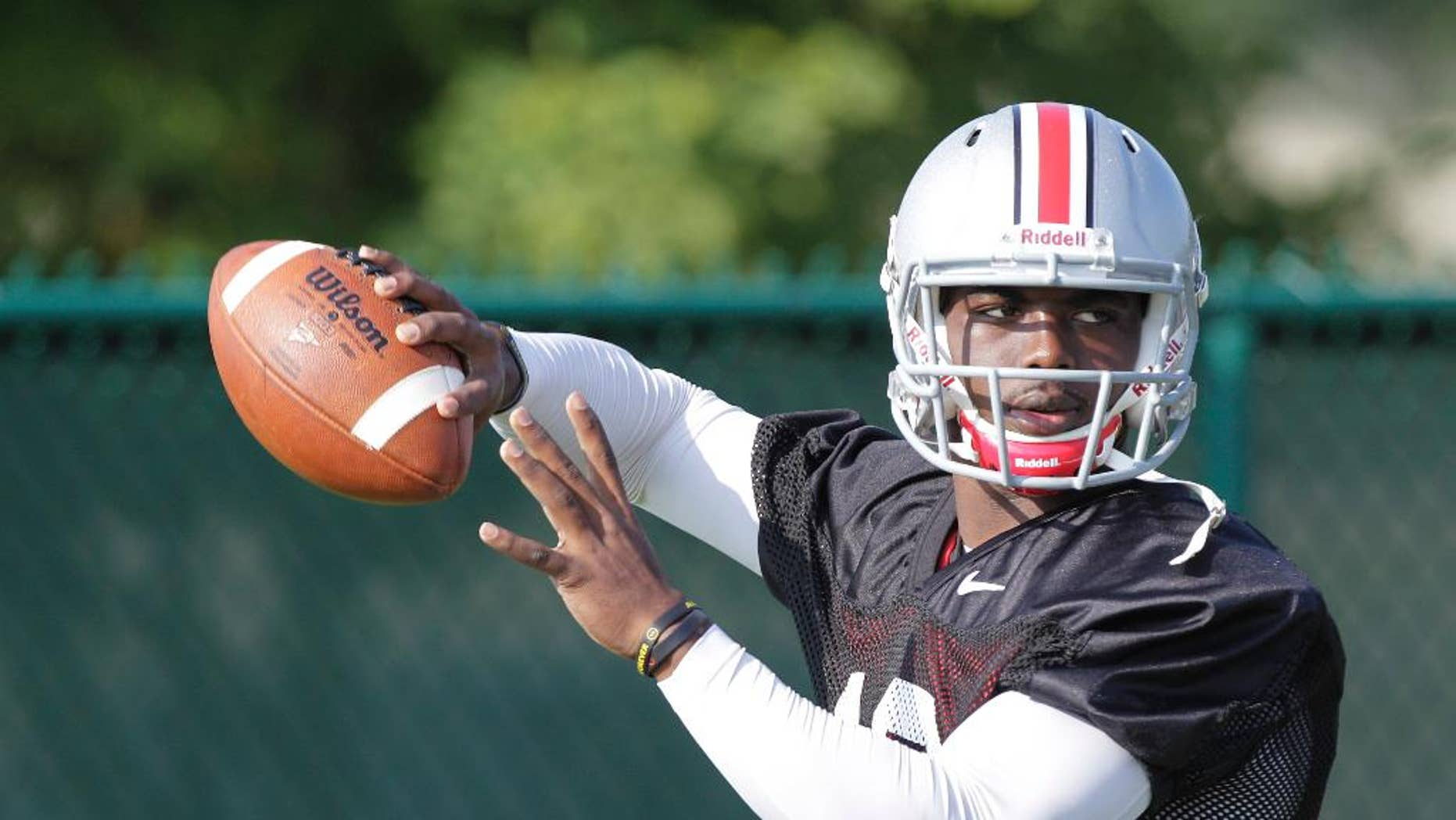 FILE - In this Aug. 9, 2014, file photo, Ohio State quarterback J.T. Barrett throws a pass during NCAA college football practice in Columbus, Ohio. His teammates and coaches say Barrett has taken over as No. 5 Ohio State's starting quarterback as if that were the plan all along. It wasn't, of course. Barrett, a freshman, got the job when two-time Big Ten player of the year Braxton Miller reinjured his throwing shoulder 10 days ago and was lost for the season. (AP Photo/Jay LaPrete, File)