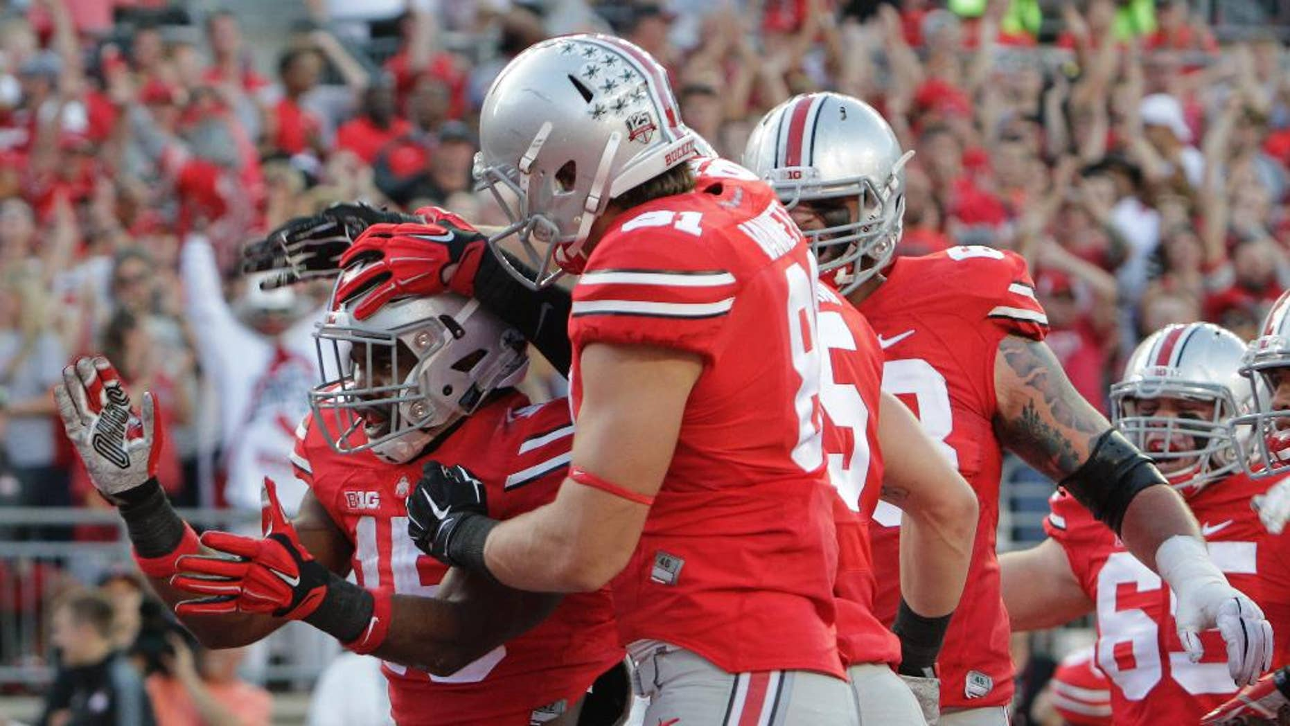 FILE - In this Sept. 27, 2014, file photo, Ohio State running back Ezekiel Elliott, left, celebrates his touchdown against Cincinnati during the first quarter of an NCAA college football game in Columbus, Ohio. All anyone wants to talk about on sports call-in shows in Ohio's capital city is No. 20 Ohio State's porous pass defense. Yet the offense has scored 116 points and piled up 1,338 yards in its last two games heading into the Big Ten opener against a leaky Maryland defense. (AP Photo/Jay LaPrete, File)