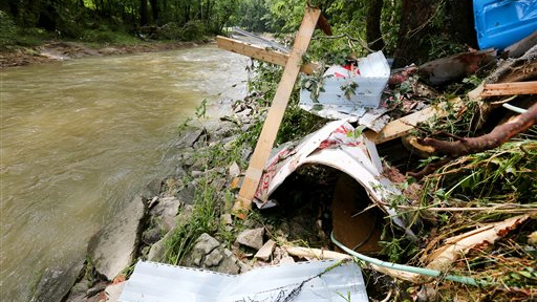 Debris rests on the bank of Red Oak Creek where a mobile home was swept off in Ripley, Ohio, Sunday, July 19, 2015.