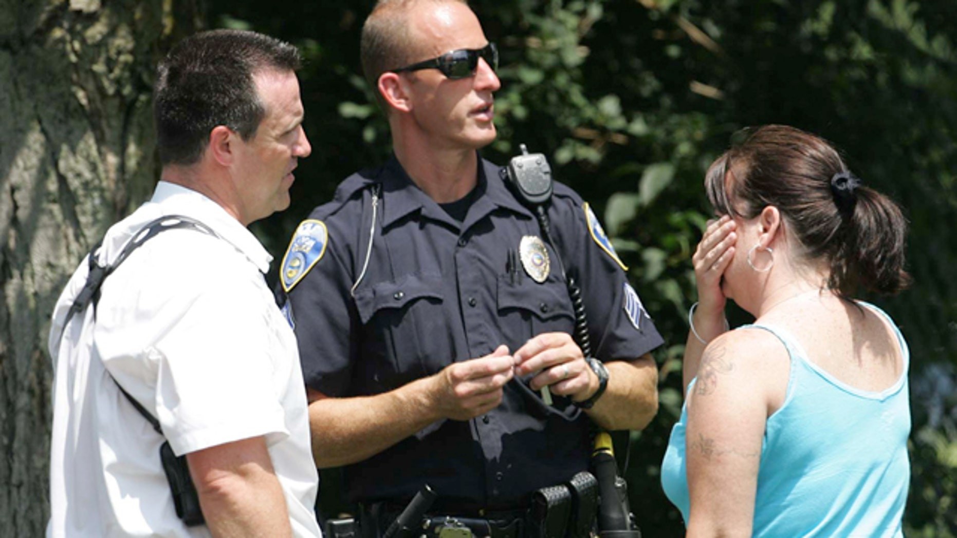 Aug. 7: Members of the Akron Police Department talk to an unidentified woman who claimed to be a relative at the scene of a multiple fatal shooting.