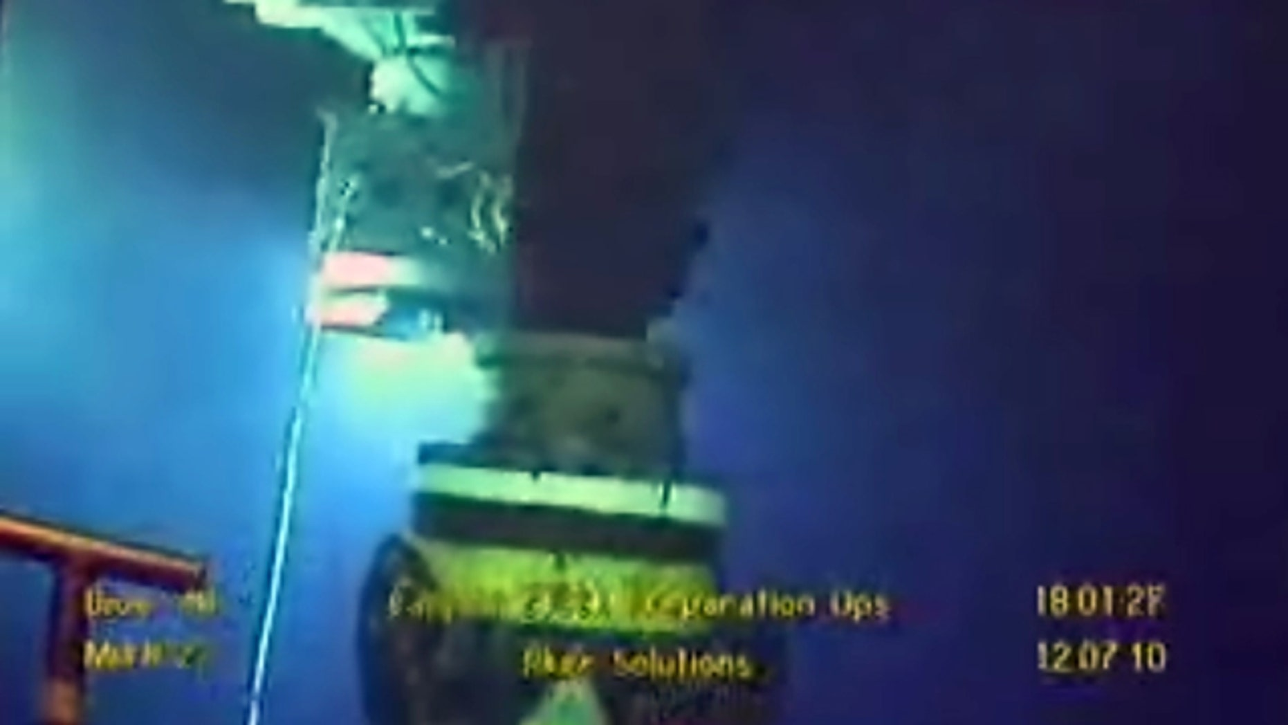 In this image taken from video provided by BP PLC at 18:01 CDT, oil flows from the broken well, center, as a new containment cap, left, hovers near the site of the Deepwater Horizon oil spill in the Gulf of Mexico, Monday, July 12, 2010. Deep-sea robots swarmed around BP's ruptured oil well Monday in a delicately choreographed effort to attach a tighter-fitting cap that could finally stop crude from gushing into the Gulf of Mexico nearly three months into the crisis.  (AP Photo/BP PLC) NO SALES