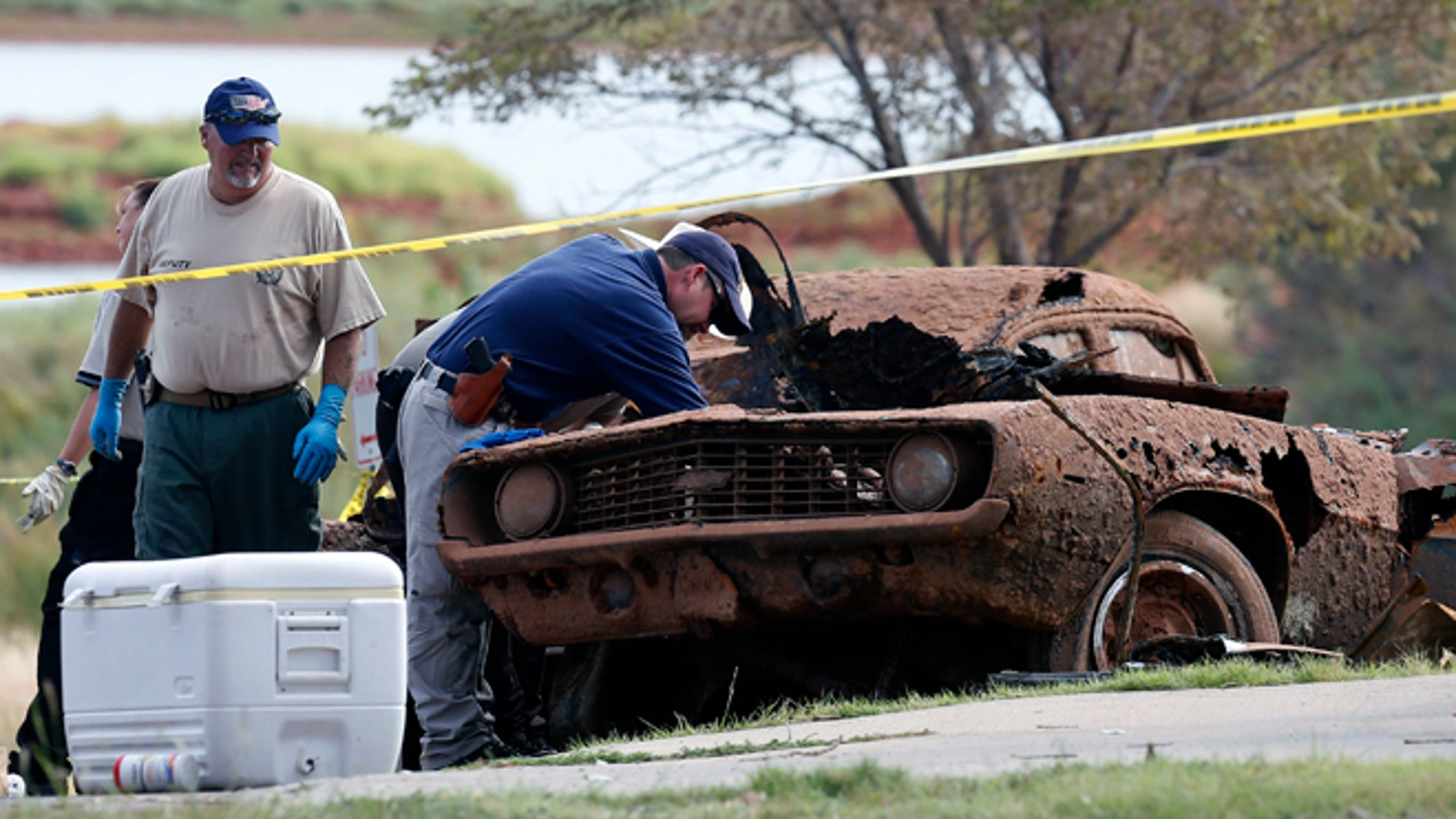 Law enforcement officials from multiple agencies examine the two cars pulled from Foss Lake, in Foss, Okla., Wednesday, Sept. 18, 2013. The Oklahoma State Medical Examinerâs Office says authorities have recovered skeletal remains of multiple bodies in the Oklahoma lake where the cars were recovered. (AP Photo/Sue Ogrocki)