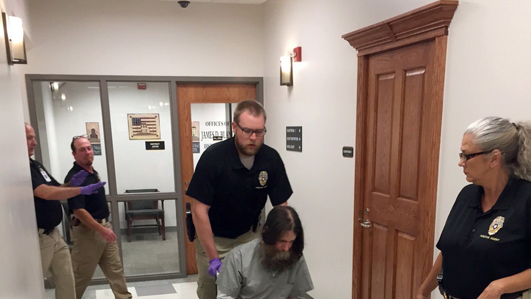 Officials transport Benjamin Robert Cole into a Pittsburg County courtroom, Friday, Aug. 28, 2015, in McAlester, Okla., before a hearing about his sanity. Cole is scheduled to die for killing his 9-month-old daughter in 2002. (AP Photo/Sean Murphy)