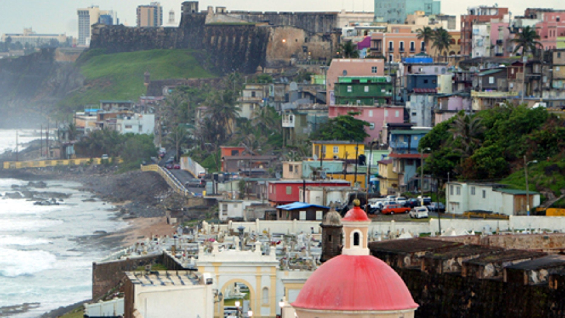 SAN JUAN, PUERTO RICO- APRIL 26: The cupola of San Juan Cemetary as well as colorful homes sit next to the ocean April 26, 2004 in Old San Juan, the original capital city of San Juan, Puerto Rico. The old city is a historic district of seven square blocks made up of ancient buildings and colonial homes, massive stone walls and vast fortifications, sunny parks and cobblestoned streets.  (Photo by Joe Raedle/Getty Images)