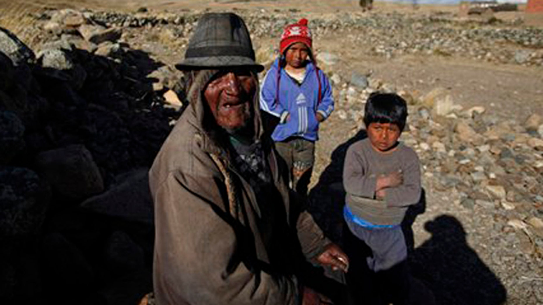 Aug 13, 2013: Carmelo Flores Laura, a native Aymara, poses for a photo with his great-grandchildren outside his home in the village of Frasquia, Bolivia.