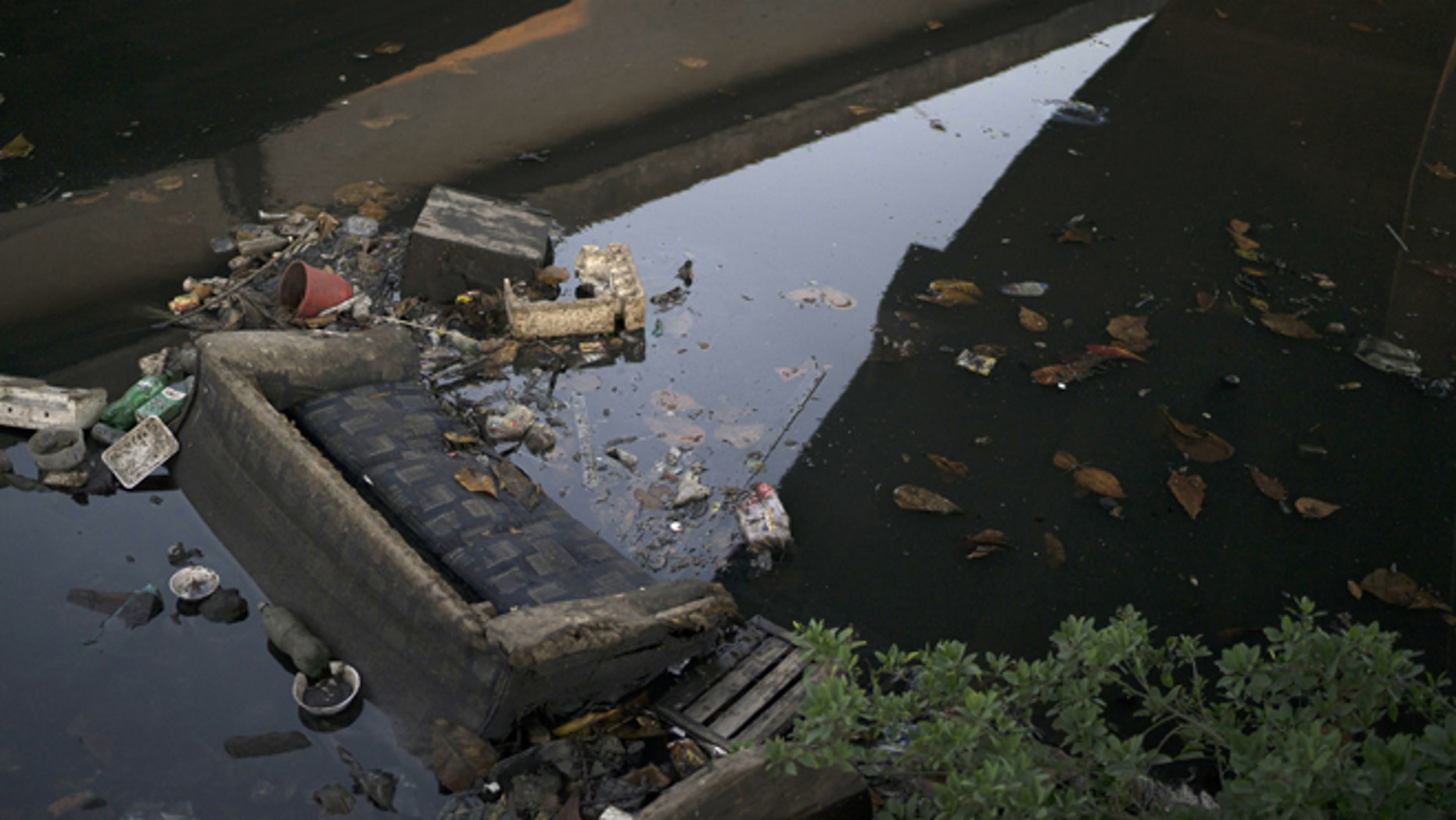 A discarded sofa lies half submerged in polluted water in a canal at the Mare slum complex  in Rio de Janeiro, Brazil, Friday, July 31, 2015. In Rio, much of the waste runs through open-air ditches to fetid streams and rivers that feed the Olympic water sites and blight the city's picture postcard beaches. (AP Photo/Leo Correa)