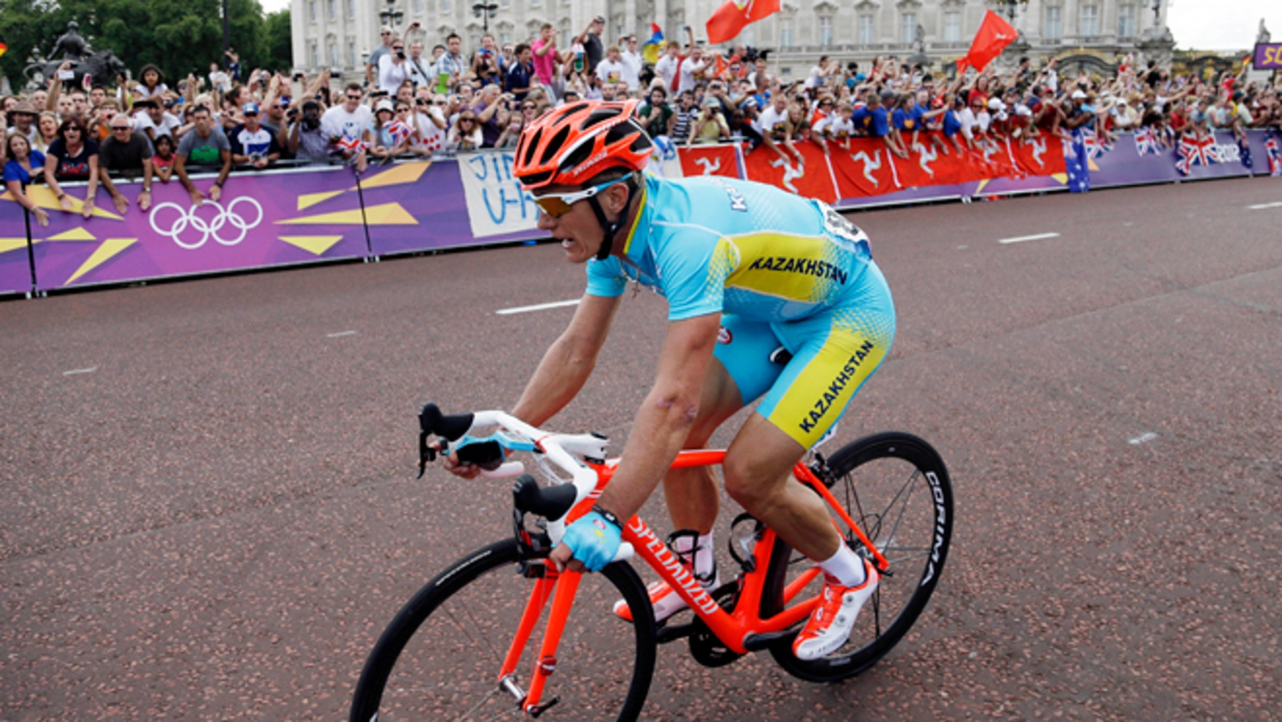 July 28, 2012: Kazakhstan's Alexandr Vinokourov pedals past Buckingham Palace on his way to win the Men's Road Cycling race at the 2012 Summer Olympics in London.
