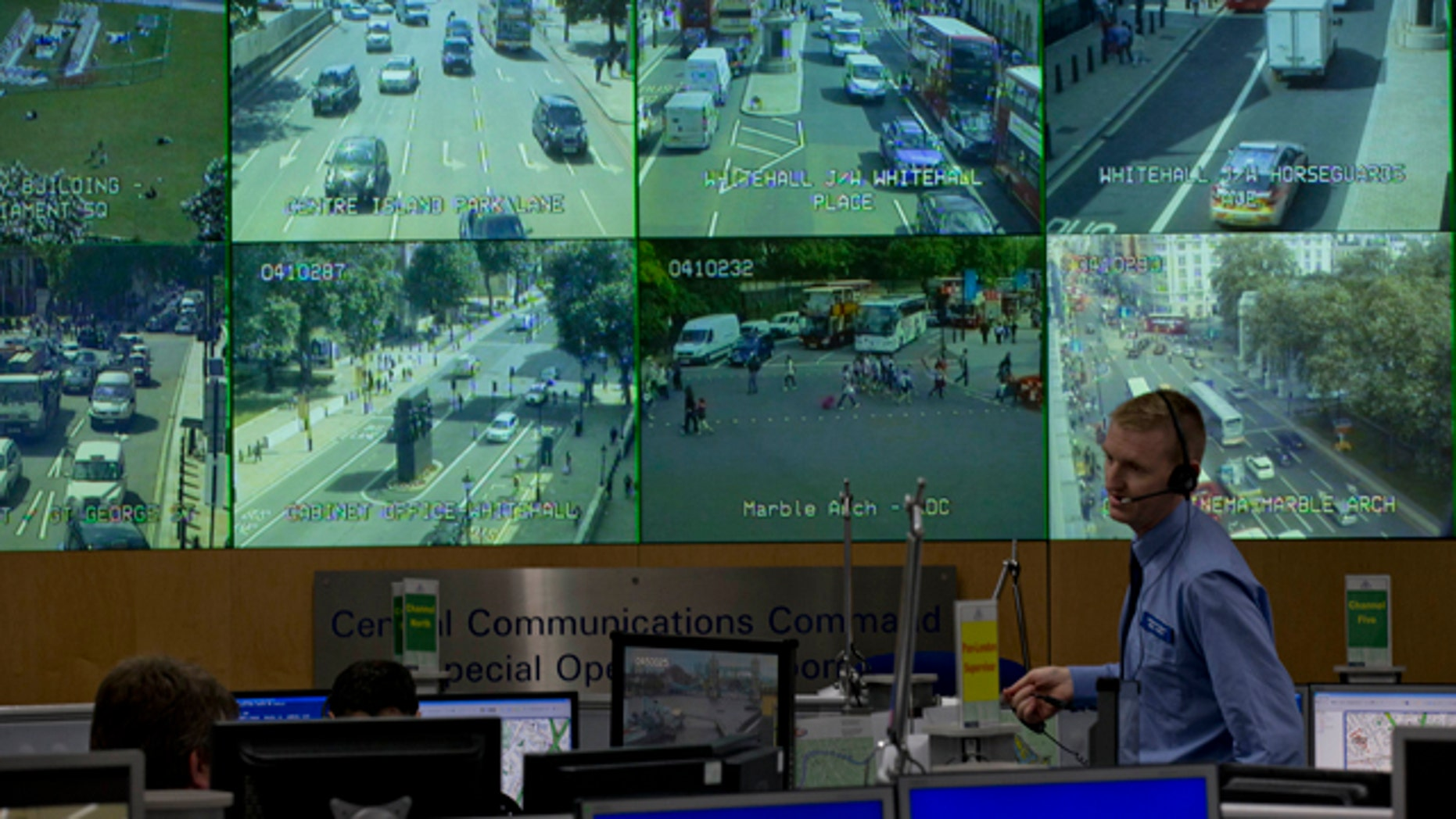 July 19, 2012: A member of police staff stands in front of CCTV screens in London's Metropolitan Police Service Special Operations Room in central London.