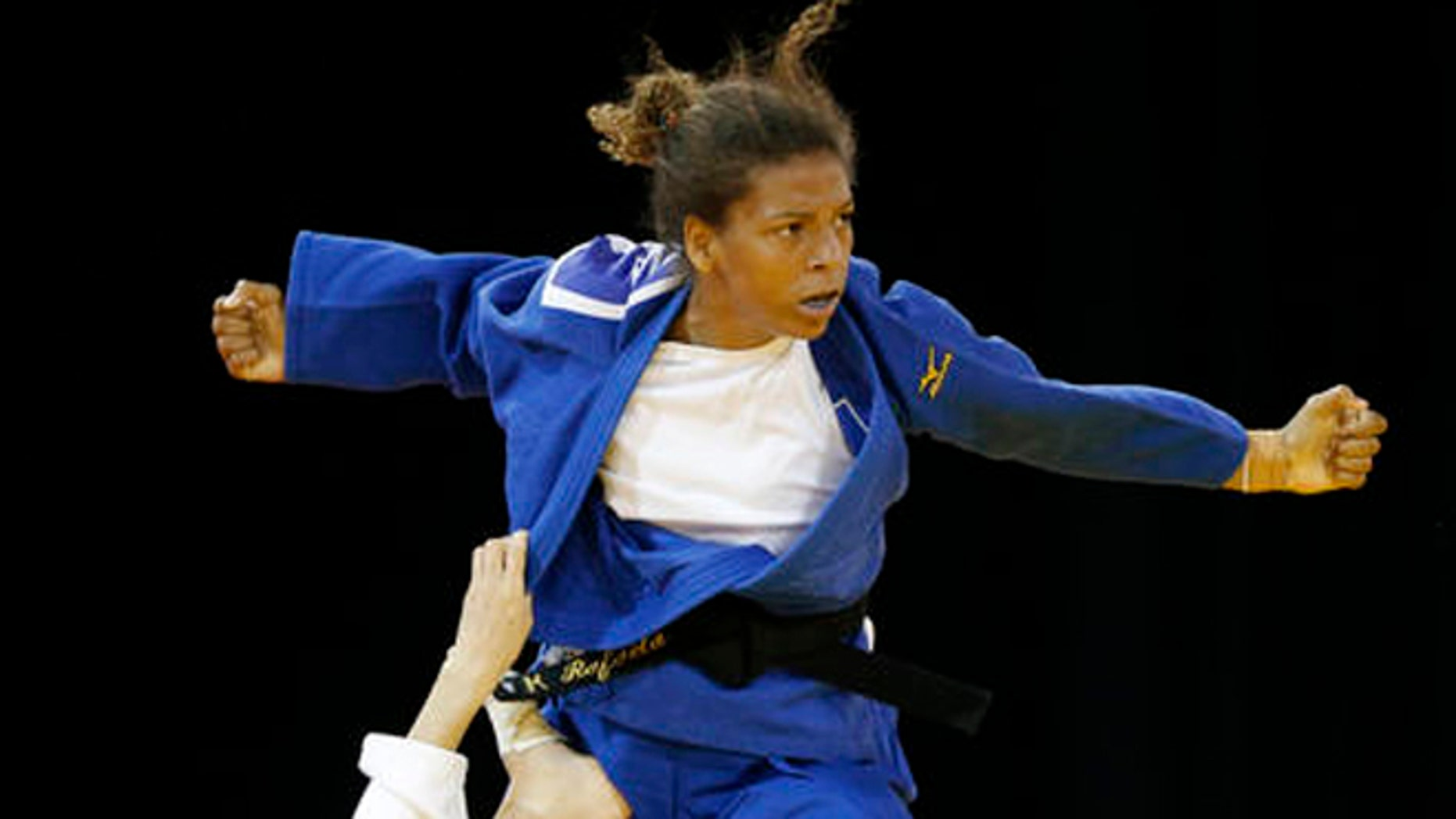 FILE - In this July 12, 2015 file photo, Brazil's Rafaela Silva, top, competes against Venezuela's Anriquelis Barrios during a women's -57kg bronze medal judo match at the Pan Am Games, in Mississauga, Ontario. Silva hoped to get an Olympic gold medal four years ago in London. Disqualified in her Olympic judo match and eliminated from the chance of winning a medal, Brazils Silva thought shed find refuge in sympathetic text messages from fans in her country. Instead, heres what she found: The place for a monkey is in a cage. You are not an Olympian. (AP Photo/Julio Cortez, File)