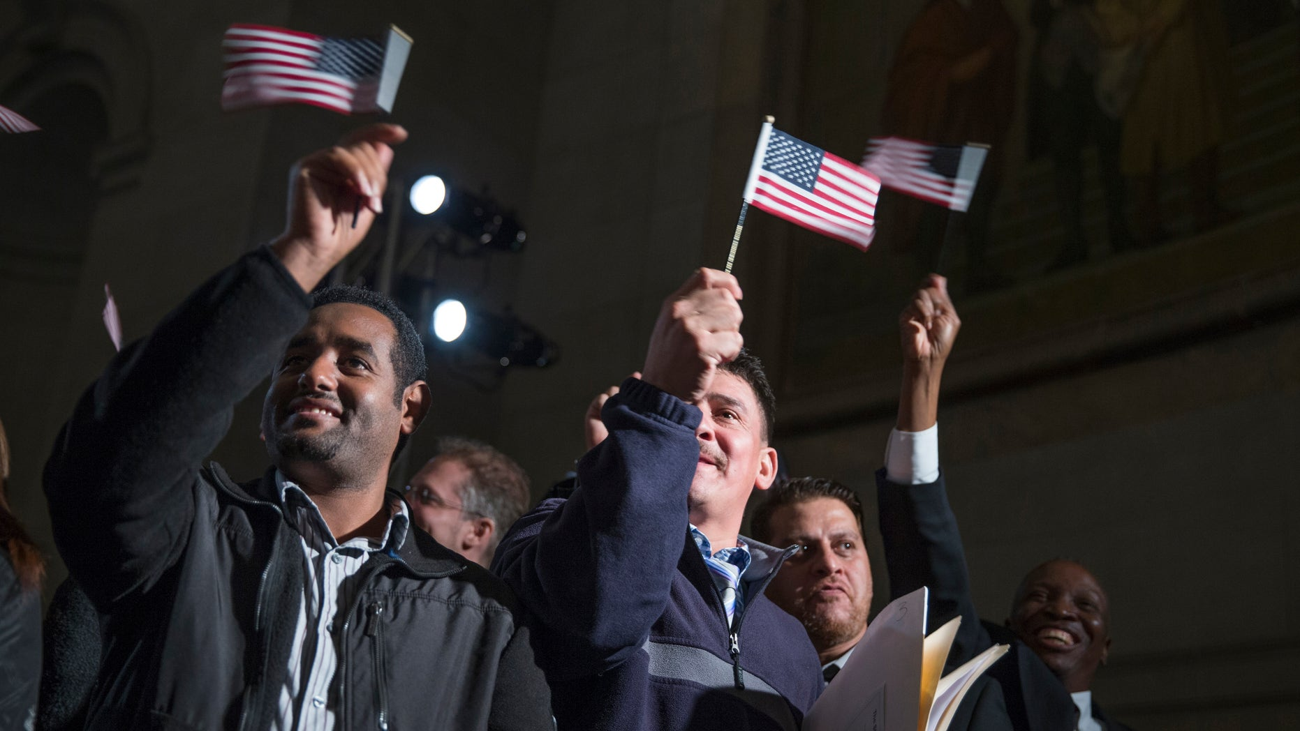 """Participants in a naturalization ceremony wave flags after taking the """"Oath of Allegiance"""" at an event attended by President Barack Obama at the National Archive in Washington, Tuesday, Dec. 15, 2015. The president spoke at the National Archives Museum, where 31 immigrants from Iraq, Ethiopia, Uganda and 23 other nations are being sworn in as U.S. citizens. (AP Photo/Evan Vucci)"""