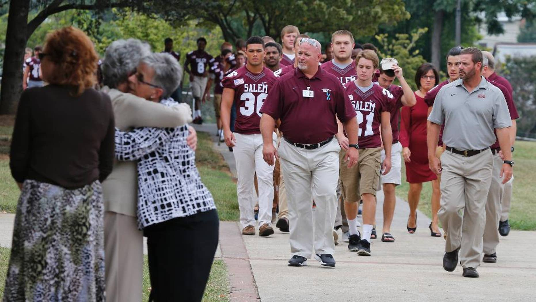 Members of the Salem High school football team arrive to remember alumnus WDBJ-TV cameraman Adam Ward, as mourners hug at Salem High School in Salem, Va., Monday, Aug. 31, 2015. Ward and reporter Alison Parker were gunned down by a former co-worker during a live shot last week. Salem High School opened its doors to the community Monday to commemorate the life of alumnus Ward. (AP Photo/Steve Helber)