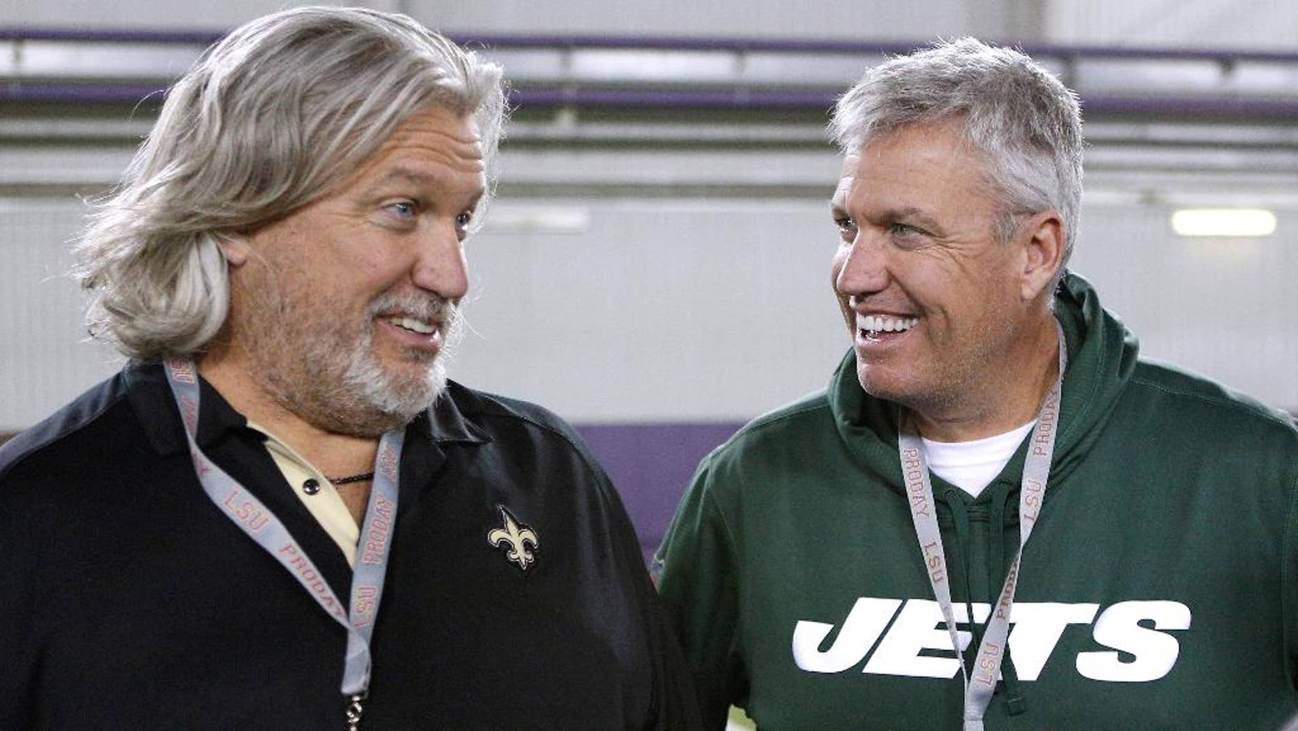 FILE - In this April 9, 2014, file photo, New Orleans Saints defensive coordinator Rob Ryan, left, and New York Jets head coach Rex Ryan talk to each other during NFL football pro day in Baton Rouge, La. The Ryan twins are best known for their defensive acumen. After four weeks, they are looking defenseless. Rex's Jets are 1-3, have lost three in a row and can't cover anyone in the passing game. Rob's Saints, he's the defensive coordinator under coach Sean Payton,  have been even worse than Rex's bunch. (AP Photo/Jonathan Bachman, File)