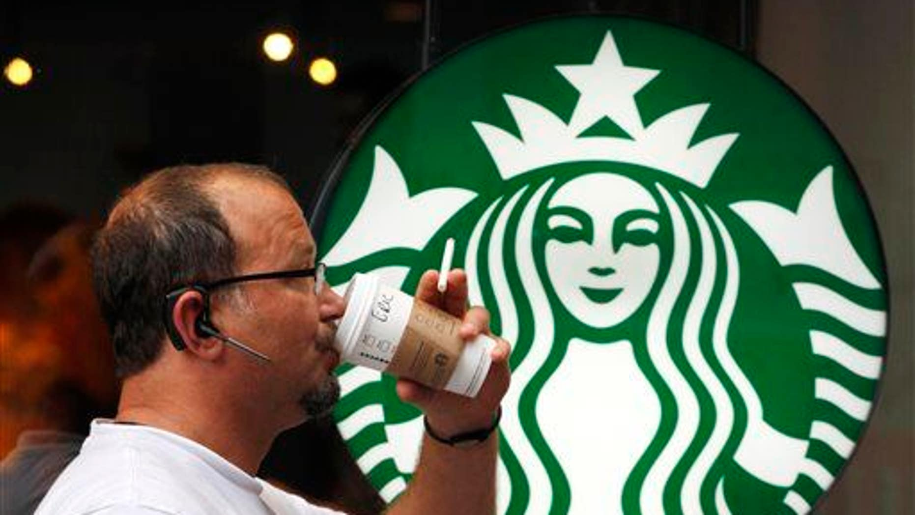 In this July 11, 2013, file photo, a man drinks a Starbucks beverage in New York.