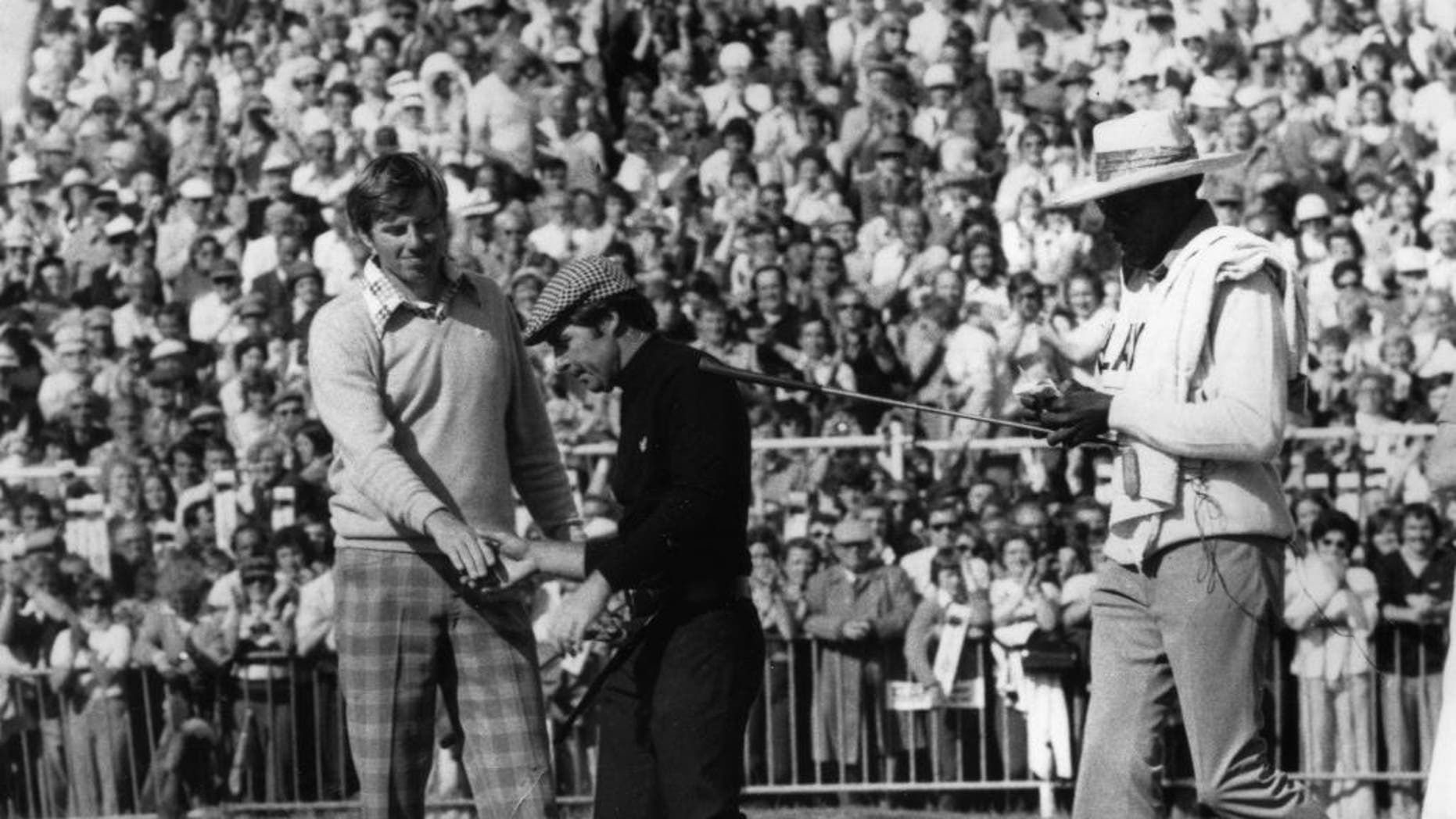 FILE - In this July 13, 1974, file photo, Gary Player, center, and Peter Oosterhuis shake hands after the final of the British Open Championship at Royal Lytham and St. Anne's in Lancashire, England. Oosterhuis, 67, said on Monday, June 29, 2015, that he has early onset Alzheimer's disease. (AP Photo, File)