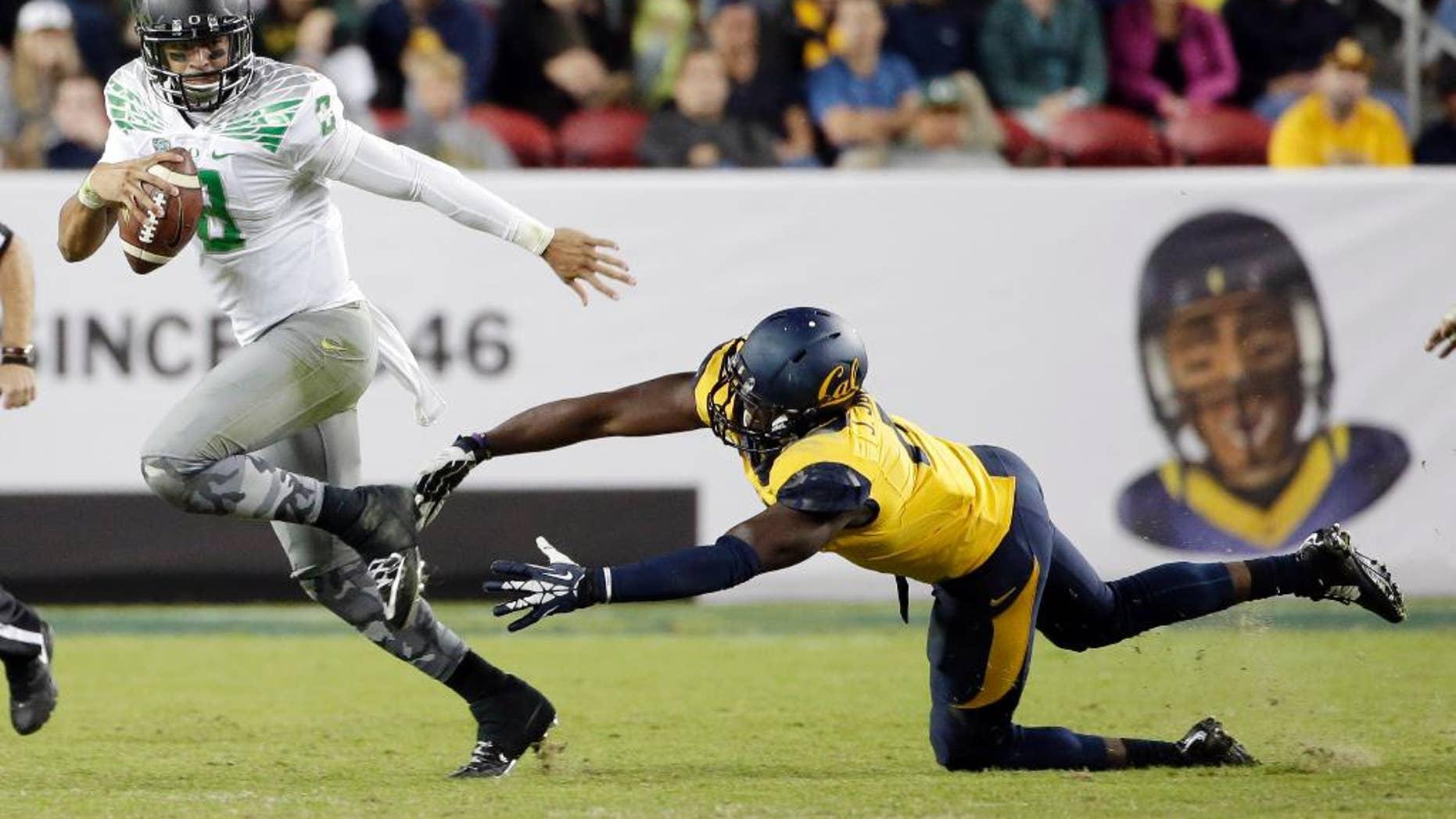 Oregon quarterback Marcus Mariota runs past California defensive end Jonathan Johnson during the second half of an NCAA college football game Friday, Oct. 24, 2014, in Santa Clara, Calif. (AP Photo/Marcio Jose Sanchez)
