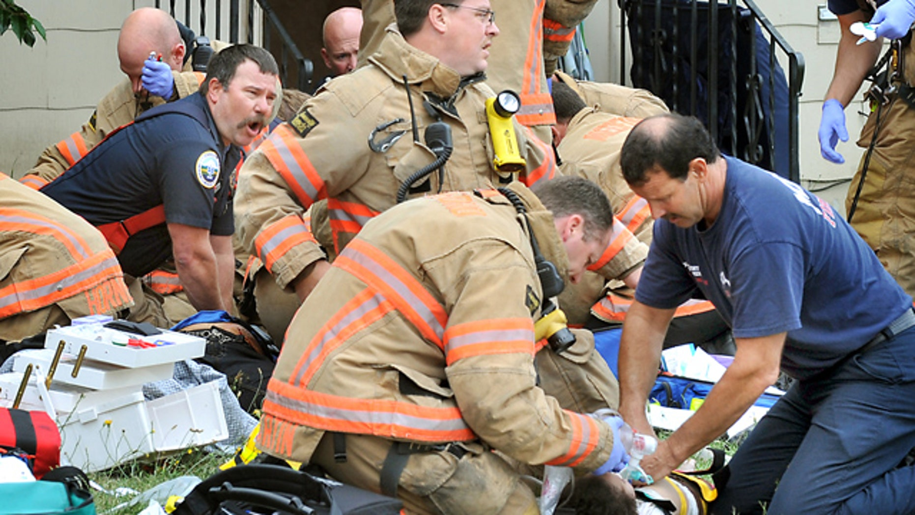 July 18, 2011: Emergency crews work to save people pulled from a burning home on West 10th Street in Medford, Ore.