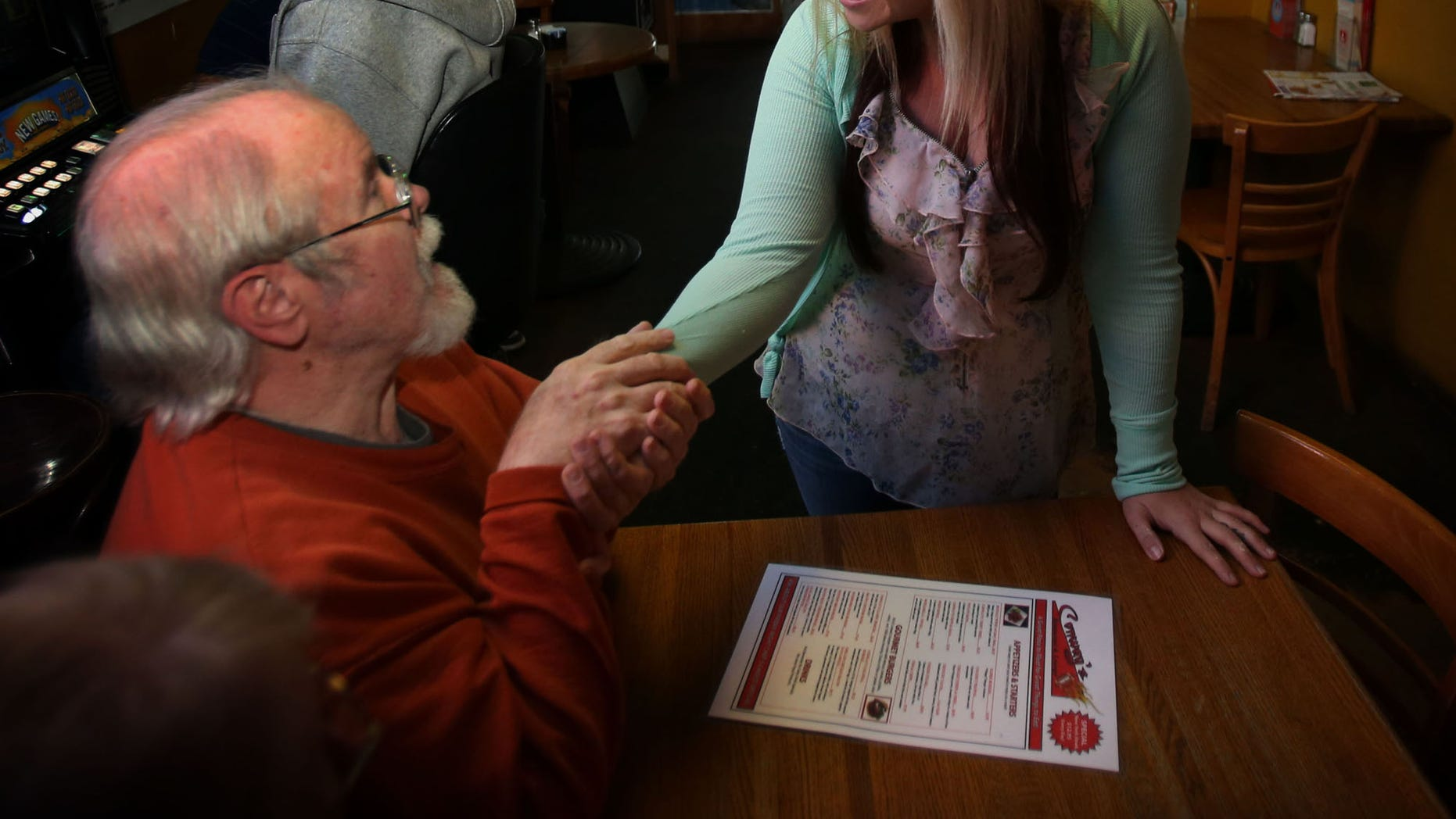 Customer Jerry Arnett, left,  congratulates  Aurora Kephart, a bartender in Springfield, Ore., Friday Oct. 4, 2013 after learning that she indirectly received a $17,500 tip when one of her customers happened to give her a winning lottery ticket this week.  The Oregon Lottery reports that one of Kephart's regular customers at Conways Restaurant gave her a couple Keno tickets on Tuesday and when she checked one was a big winner. (AP Photo/The Register-Guard, Chris Pietsch)