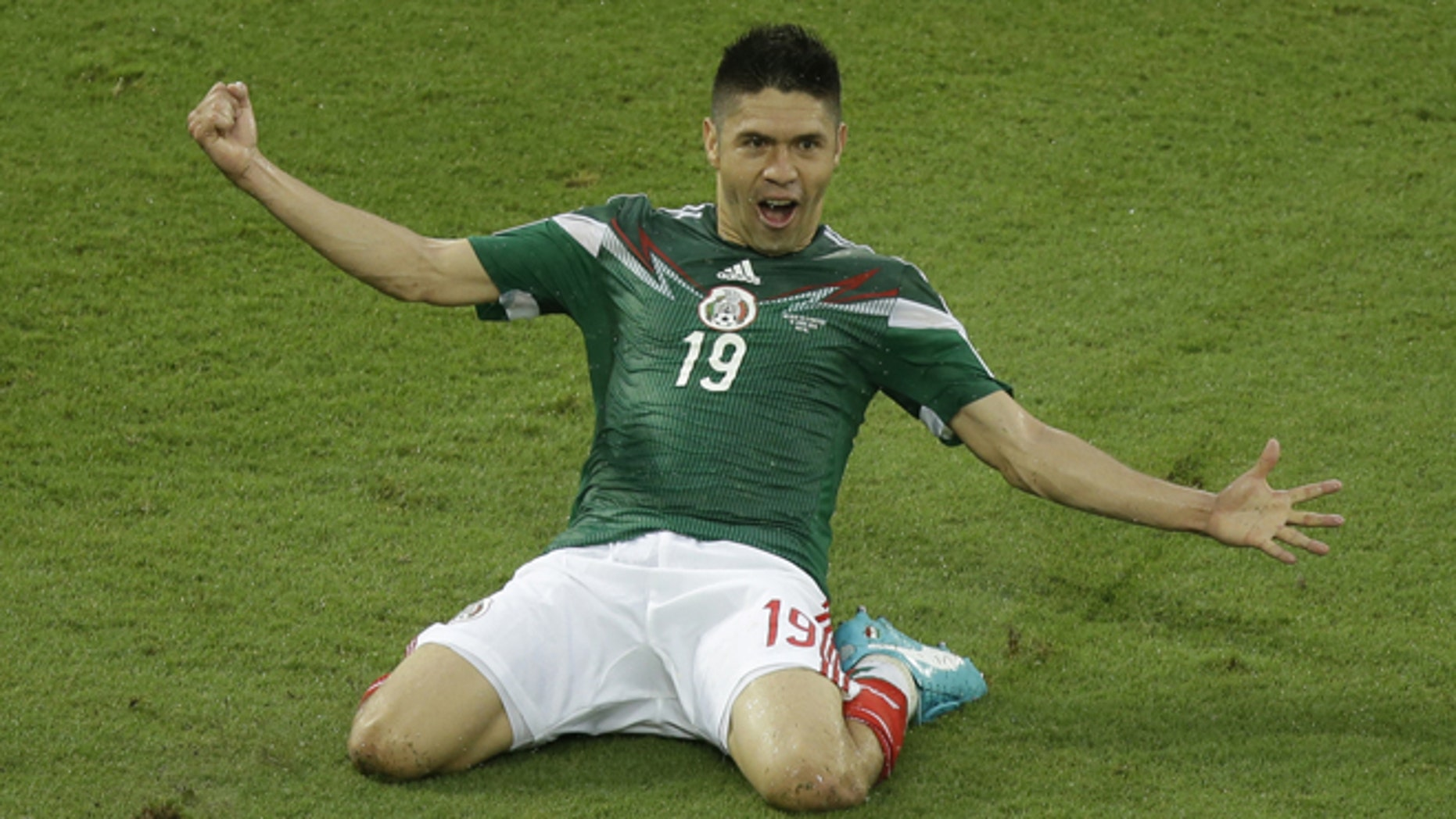 Mexico's Oribe Peralta celebrates after scoring during the group A World Cup soccer match between Mexico and Cameroon in the Arena das Dunas in Natal, Brazil, Friday, June 13, 2014.  (AP Photo/Hassan Ammar)